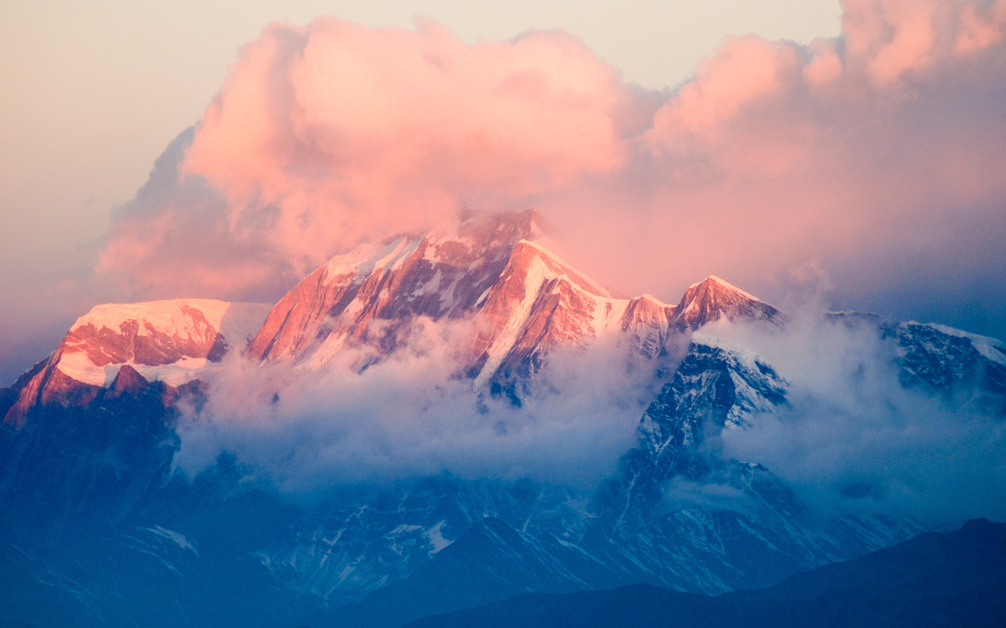 A snowy mountain bathed in pastel-colored light during sunset