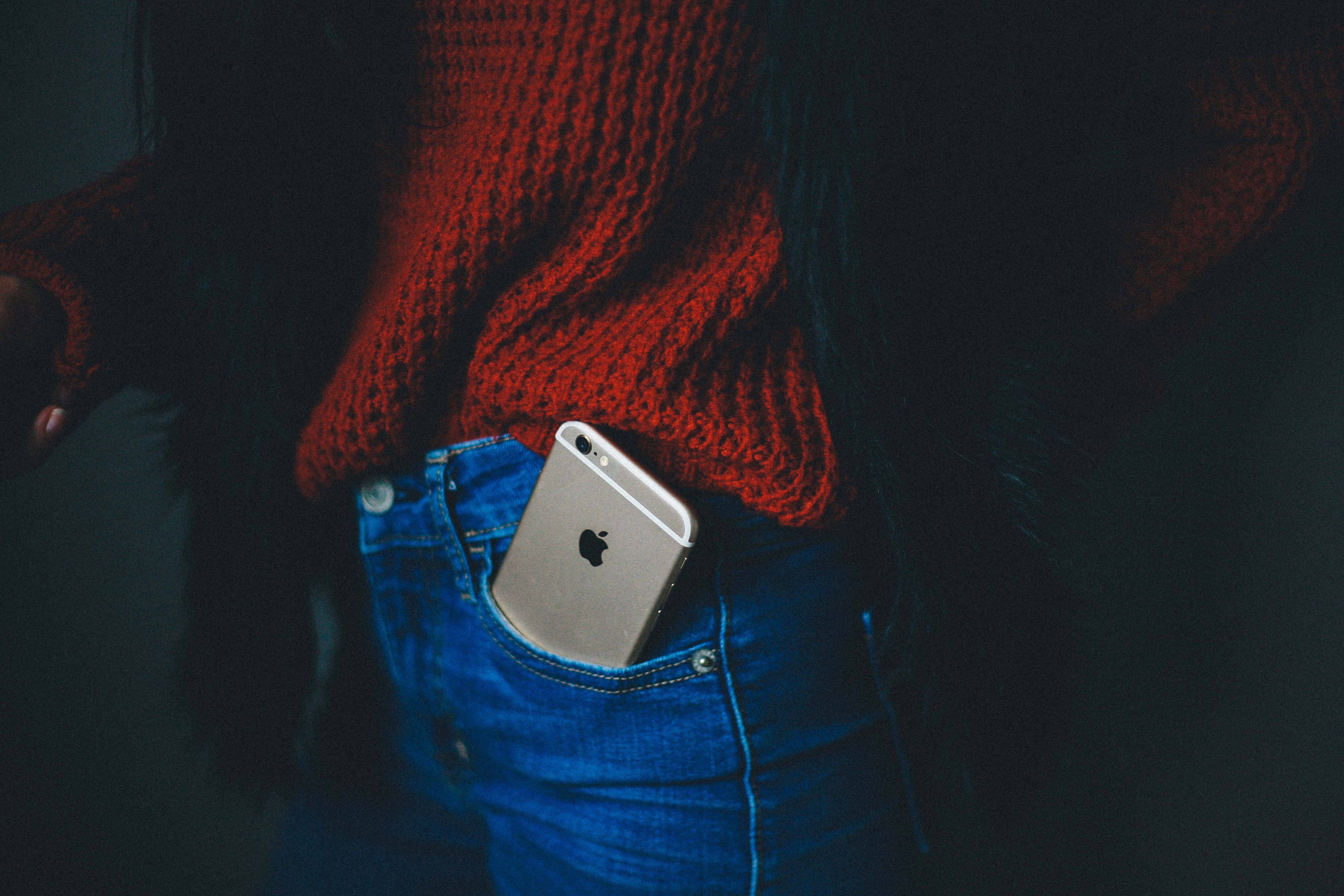 An iPhone sticking out of a pocket in a person's jeans