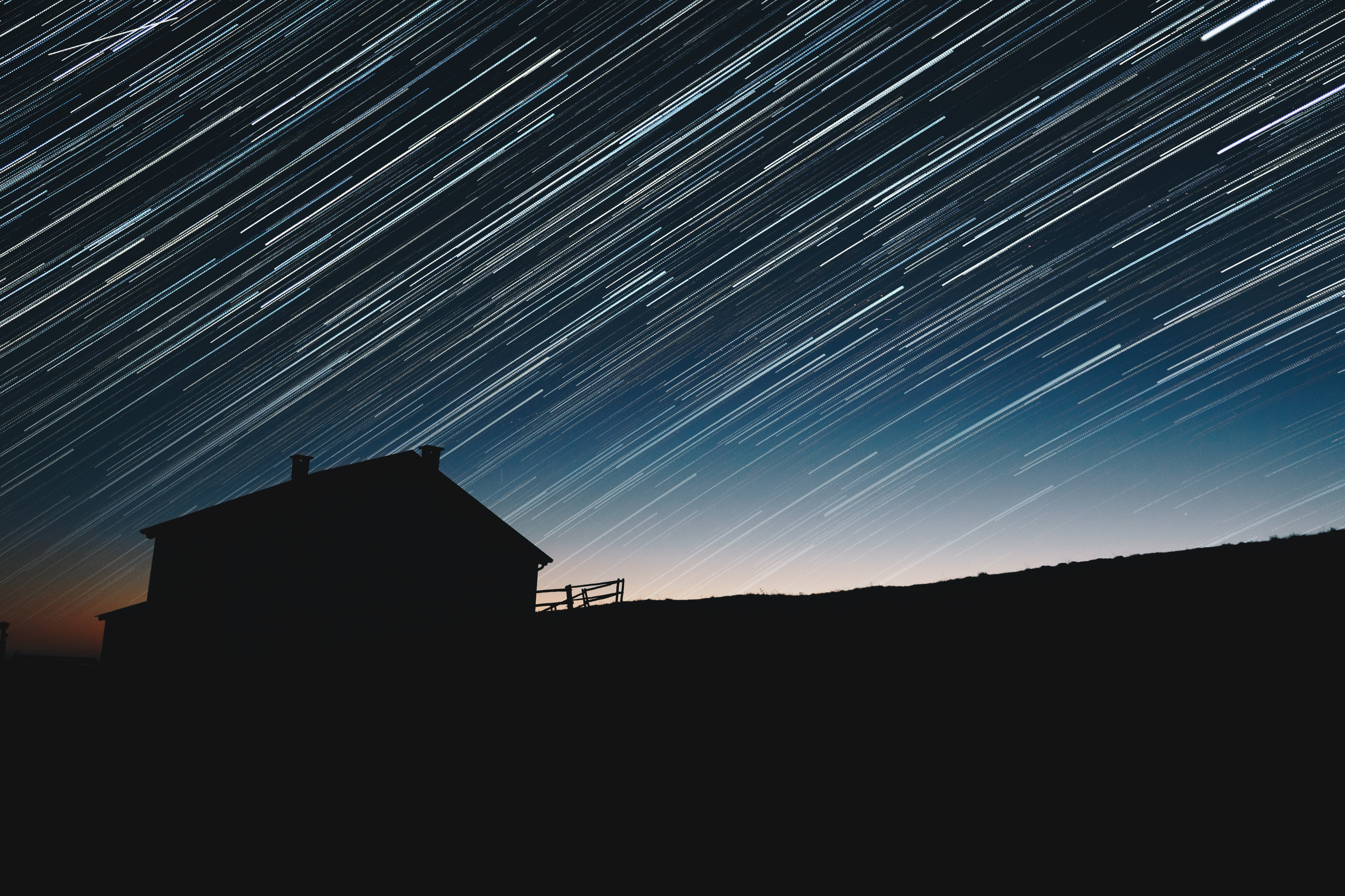Long exposure photograph of the star trails above the silhouette of a house.