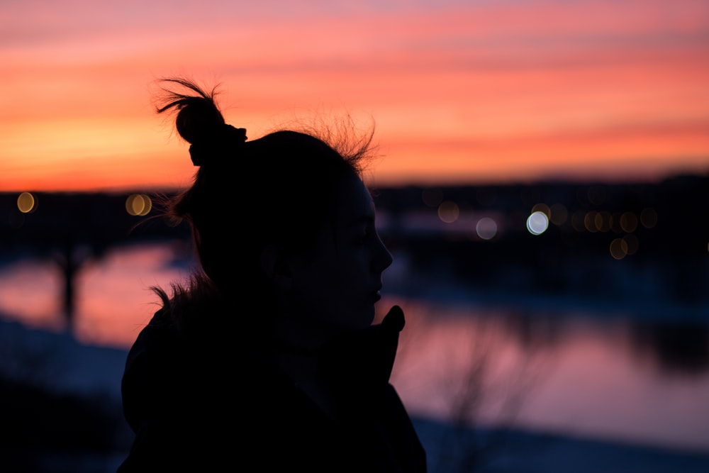 silhouette of woman near bodies of water