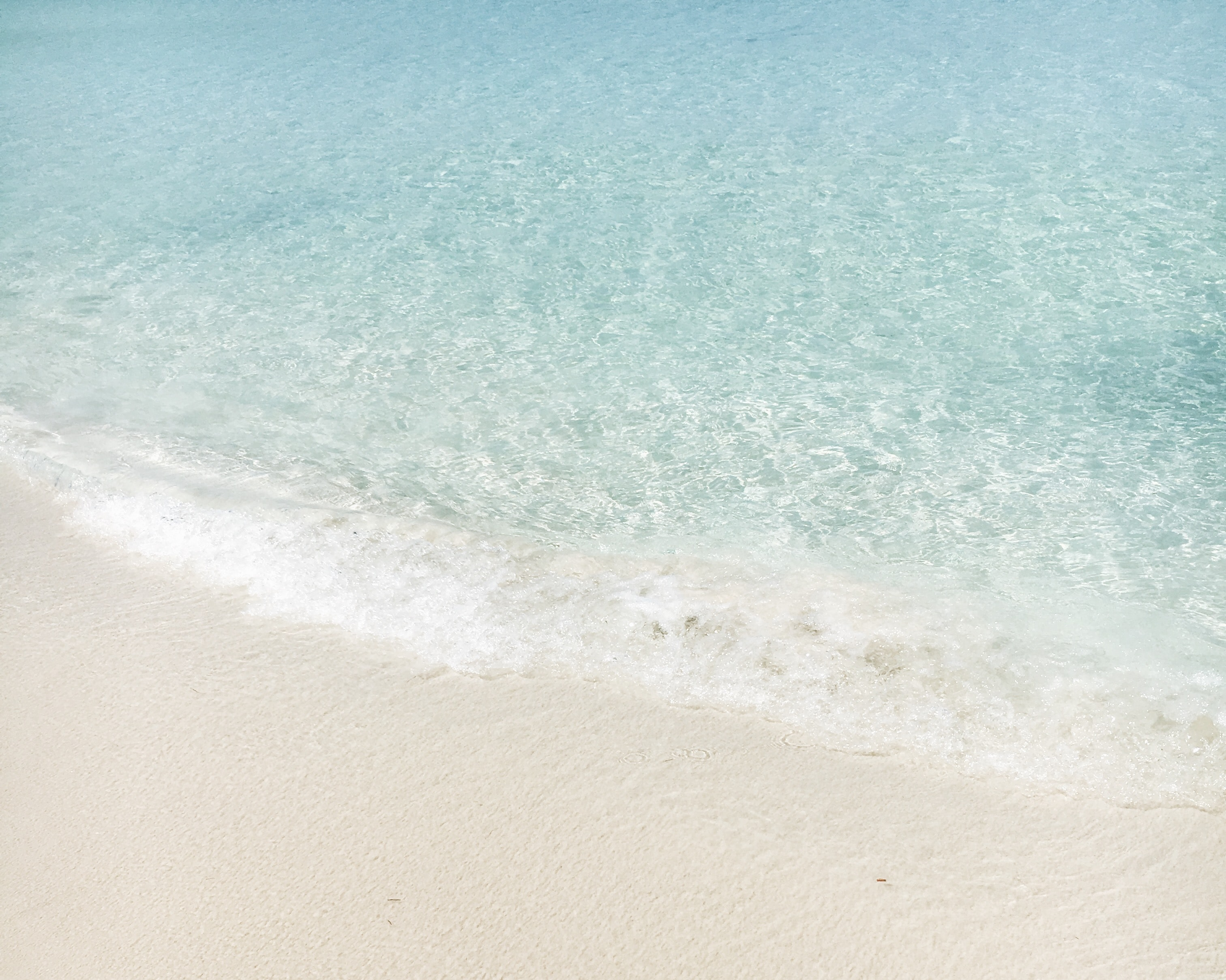 Crystal clear waves coming in on a white sandy beach.