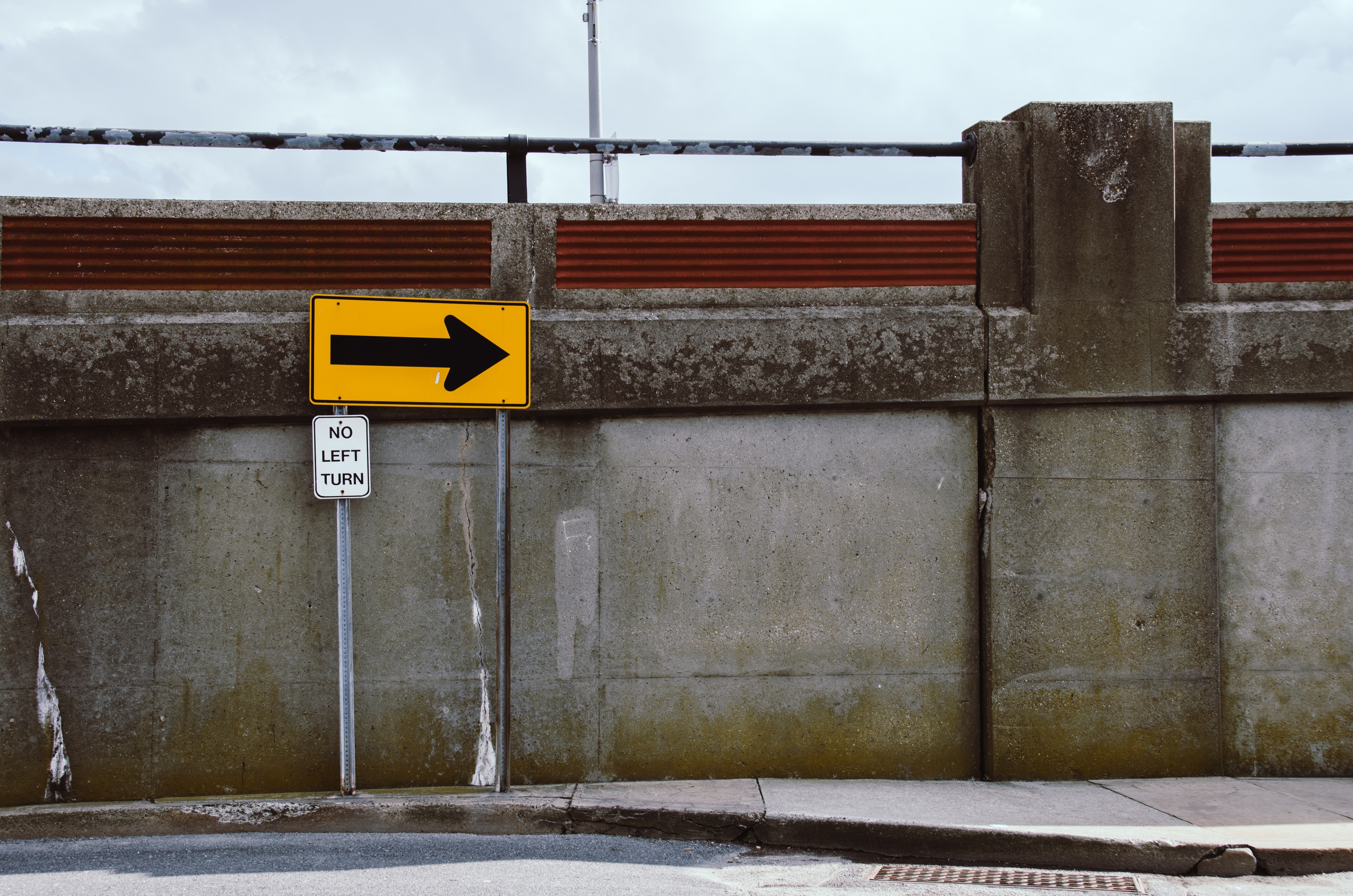 "A ""no left turn"" sign next to a concrete ledge at the side of a road"