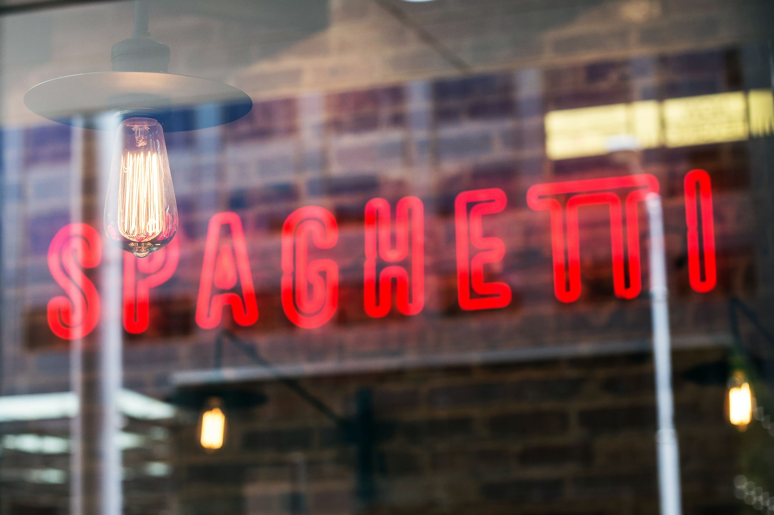 "A red neon sign reads ""SPAGHETTI"" on a wall of a restaurant seen through the window."
