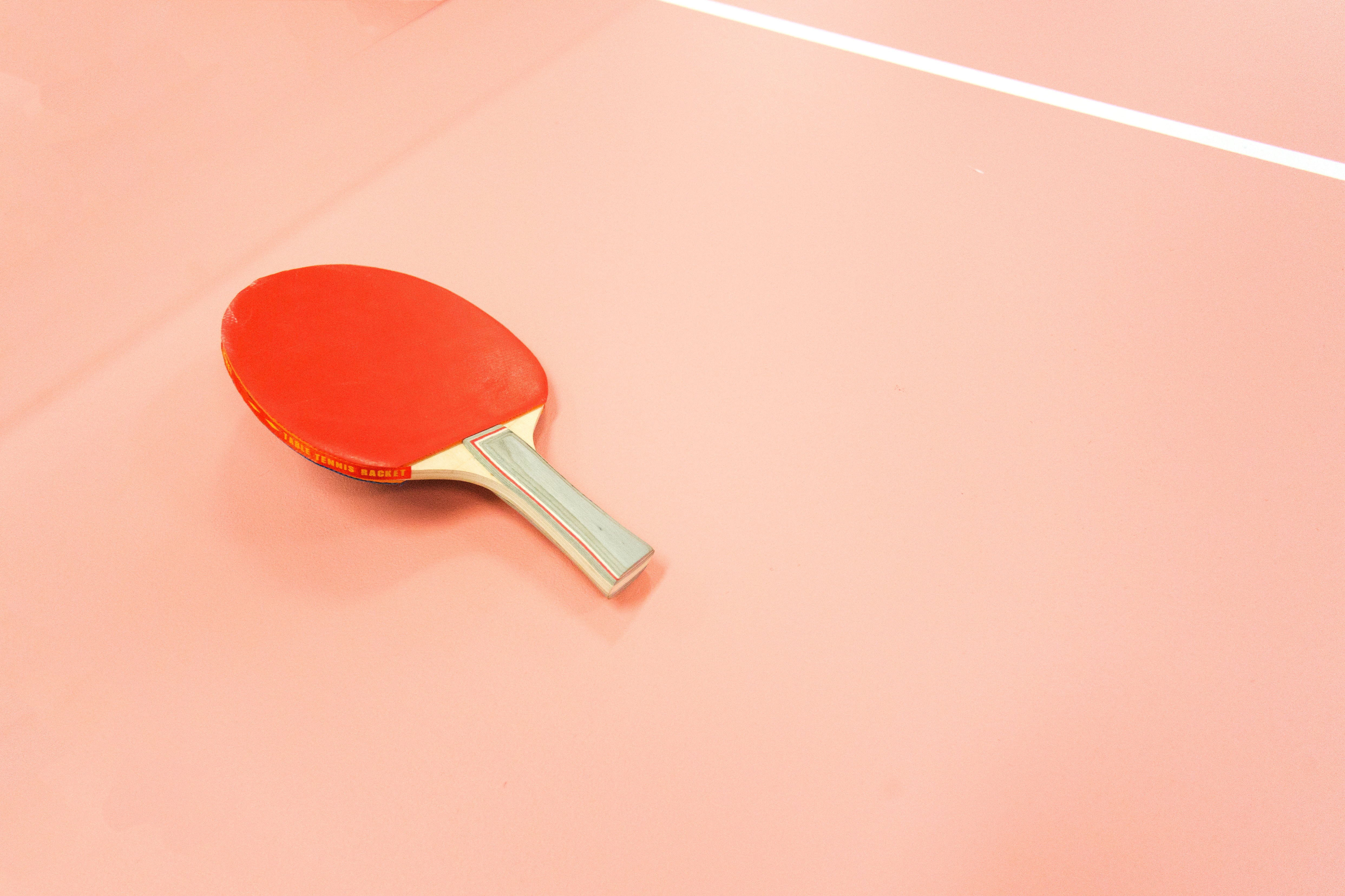 A red table tennis paddle sitting on a court.