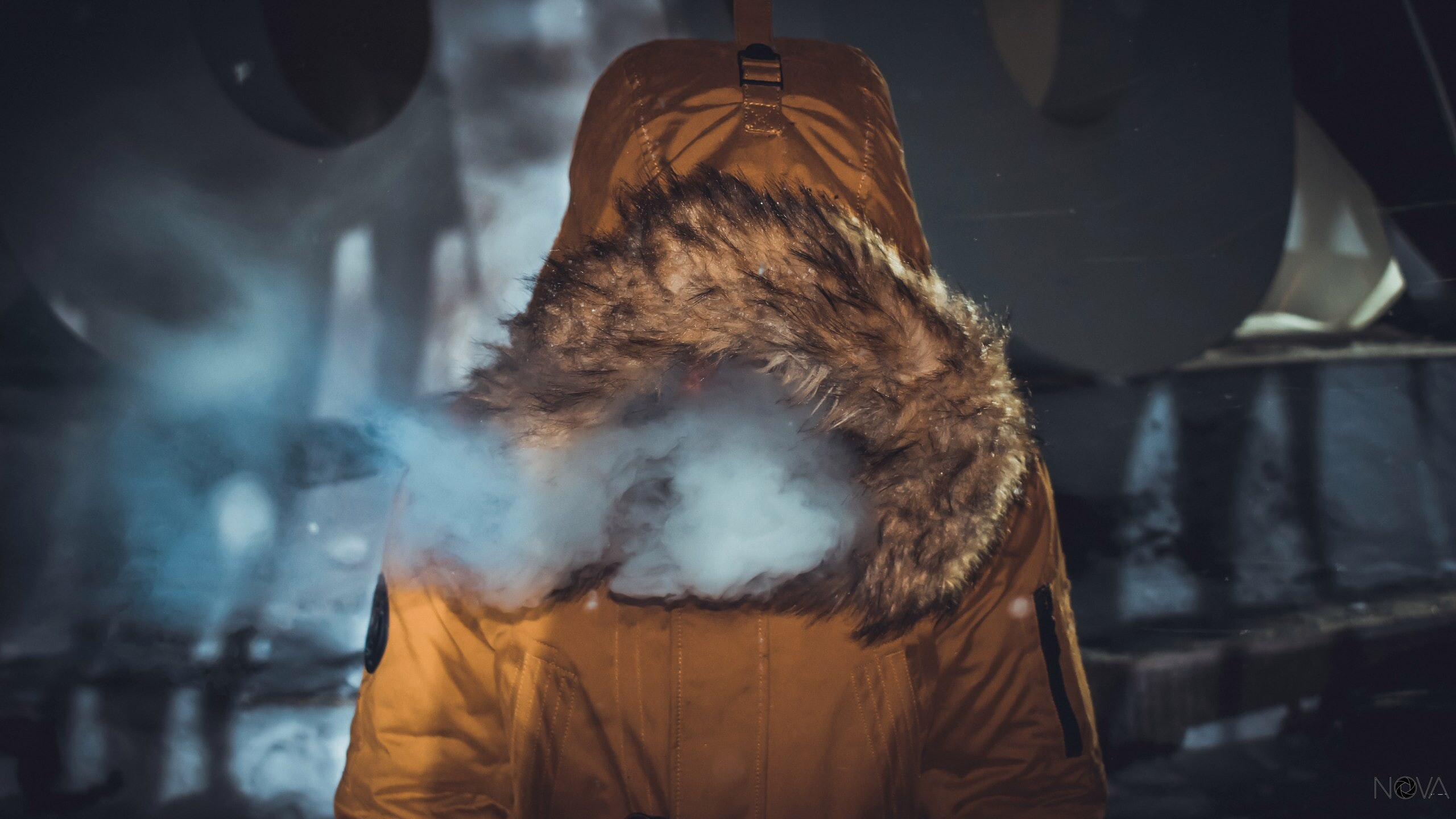 Anonymous person in a furry hooded coat exhaling smoke