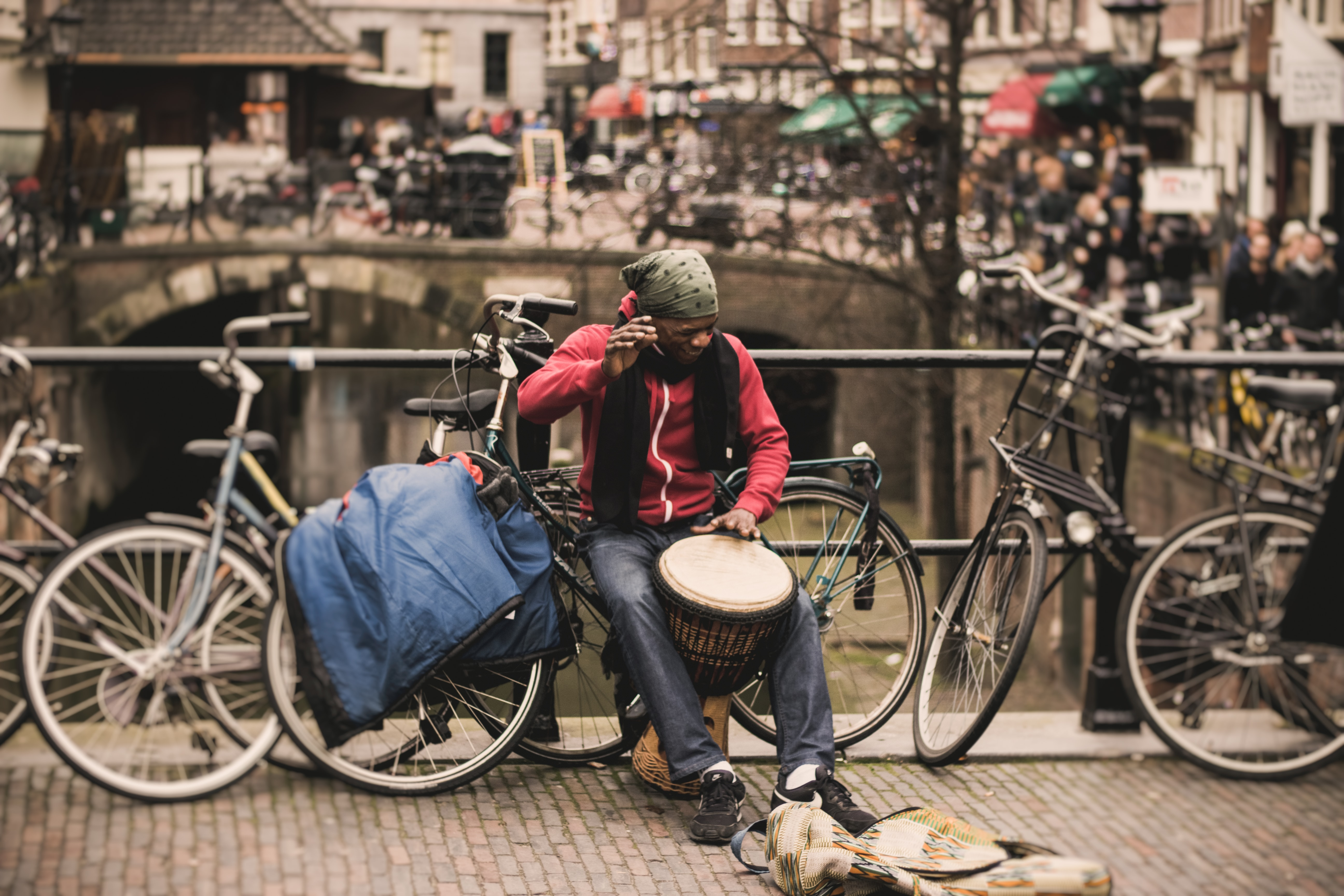 A male busker in a bandana with a bongo drum smiles while talking on the phone on a bridge