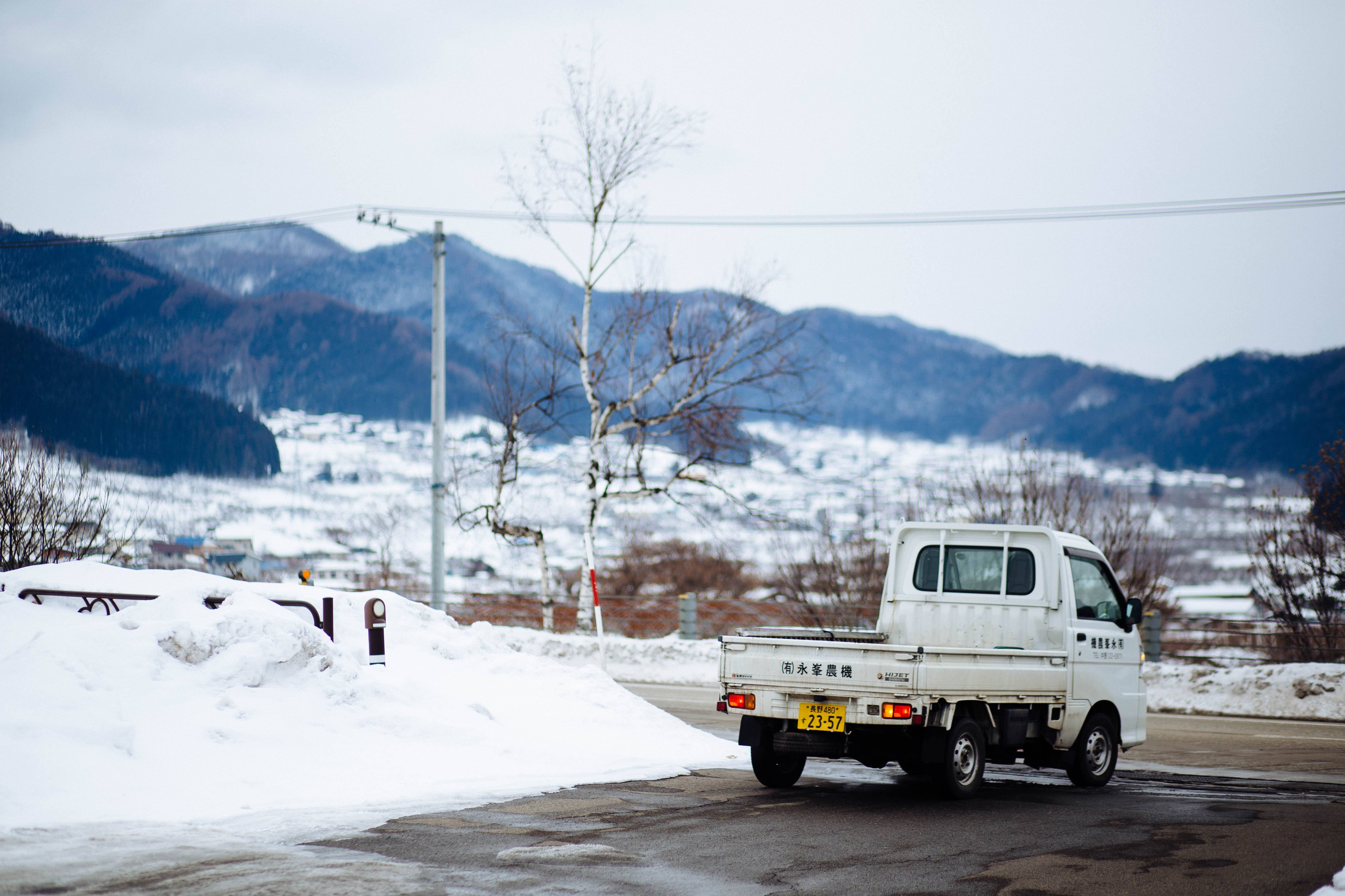 white drop side truck on road during winter season