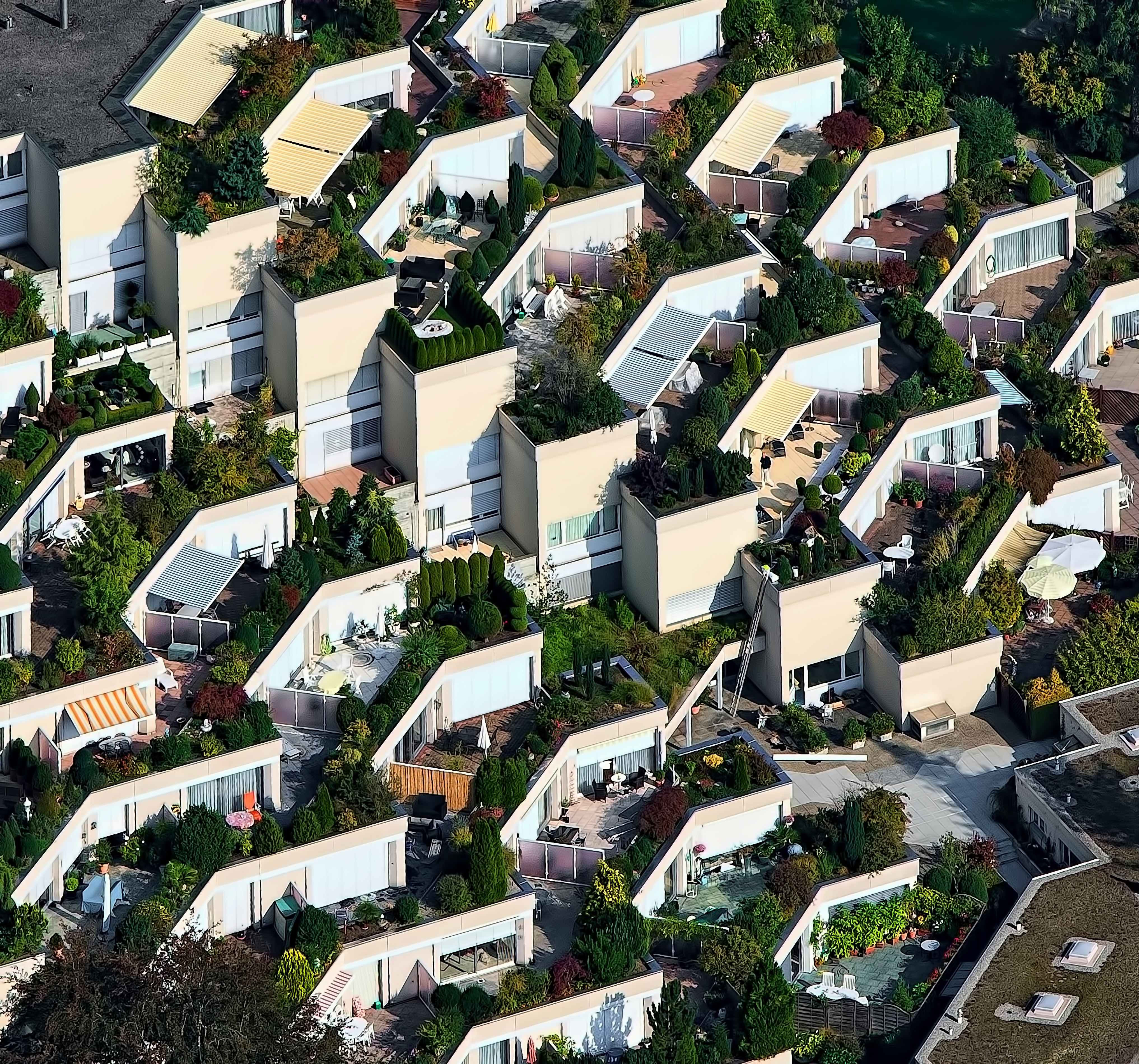 A drone shot of a housing estate with beautiful gardens on building roofs