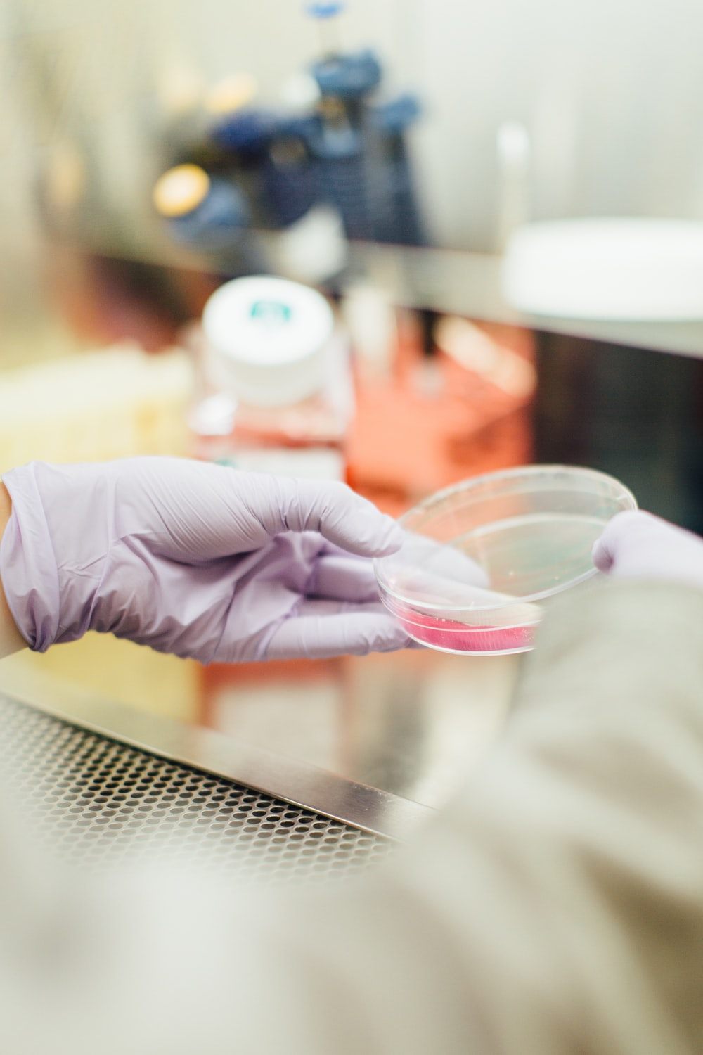 A scientist in rubber gloves holding a Petri dish with some liquid