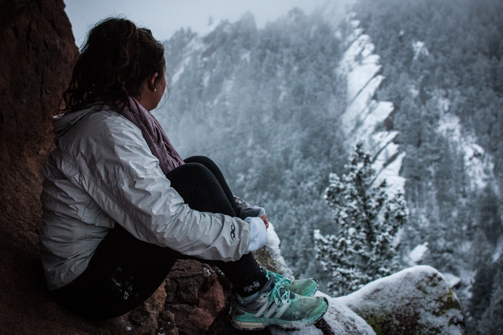 woman sitting on rock formation under snow