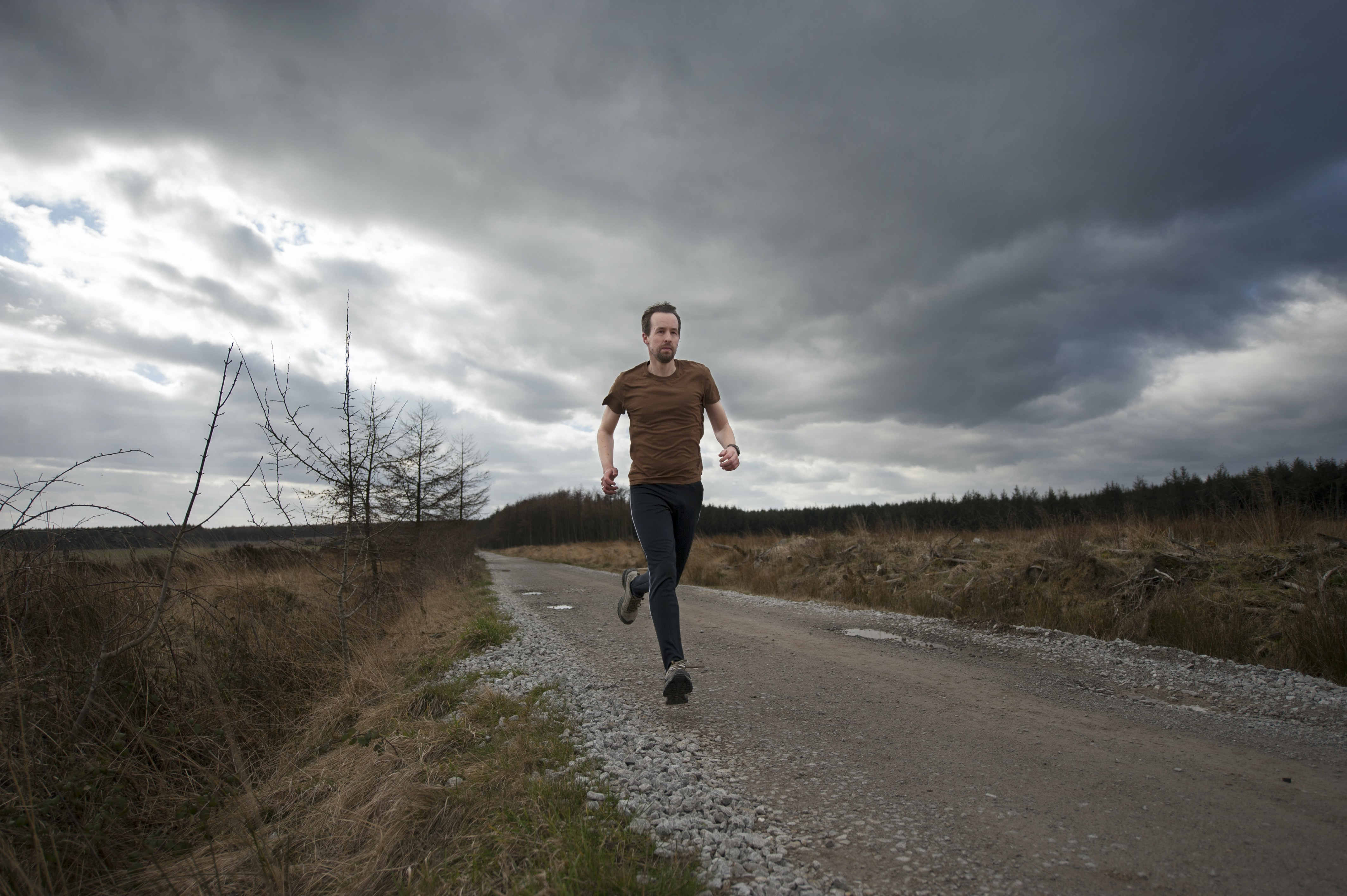 man running at the road during daytime
