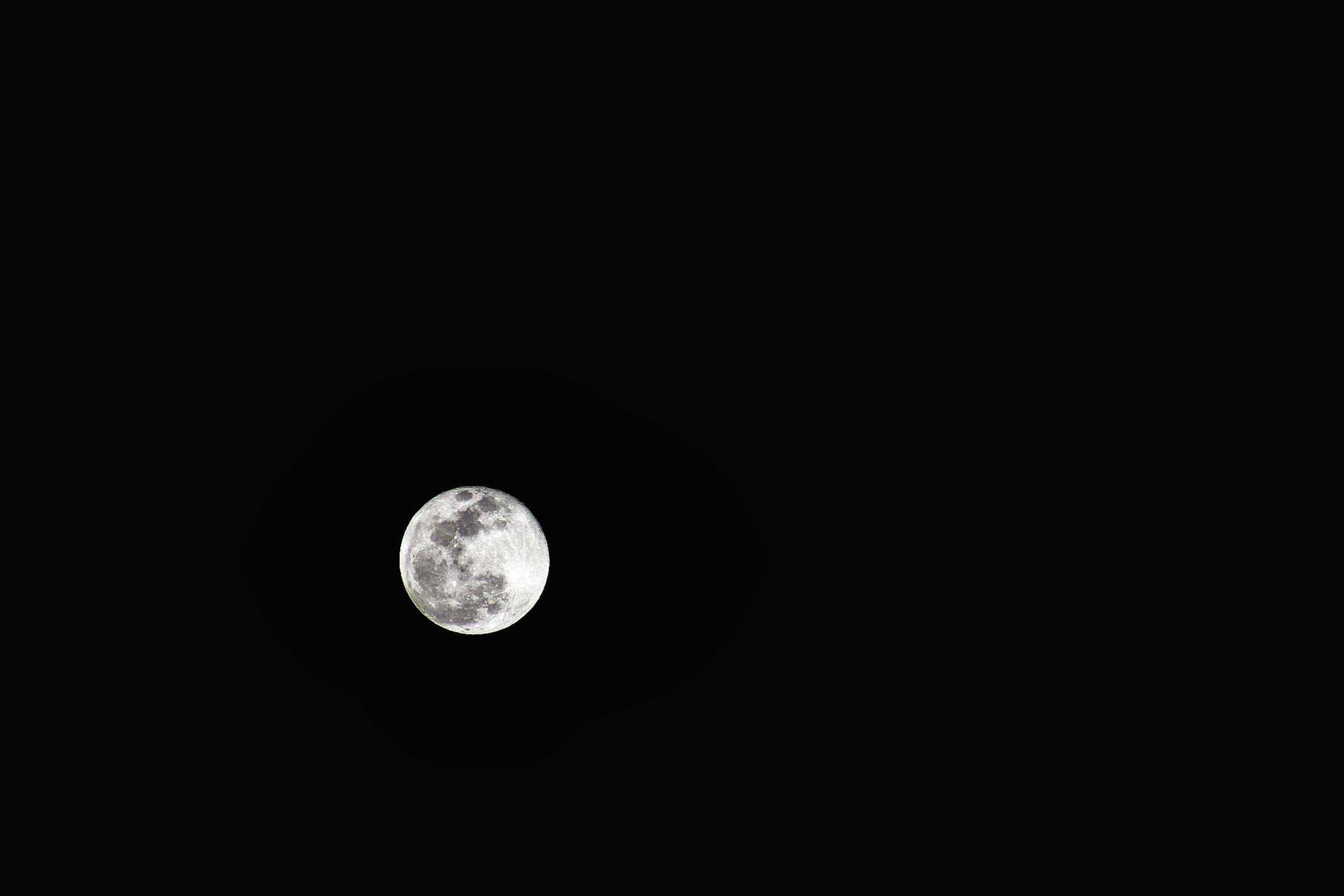 The black and white spots visible on the moon on a dark night sky