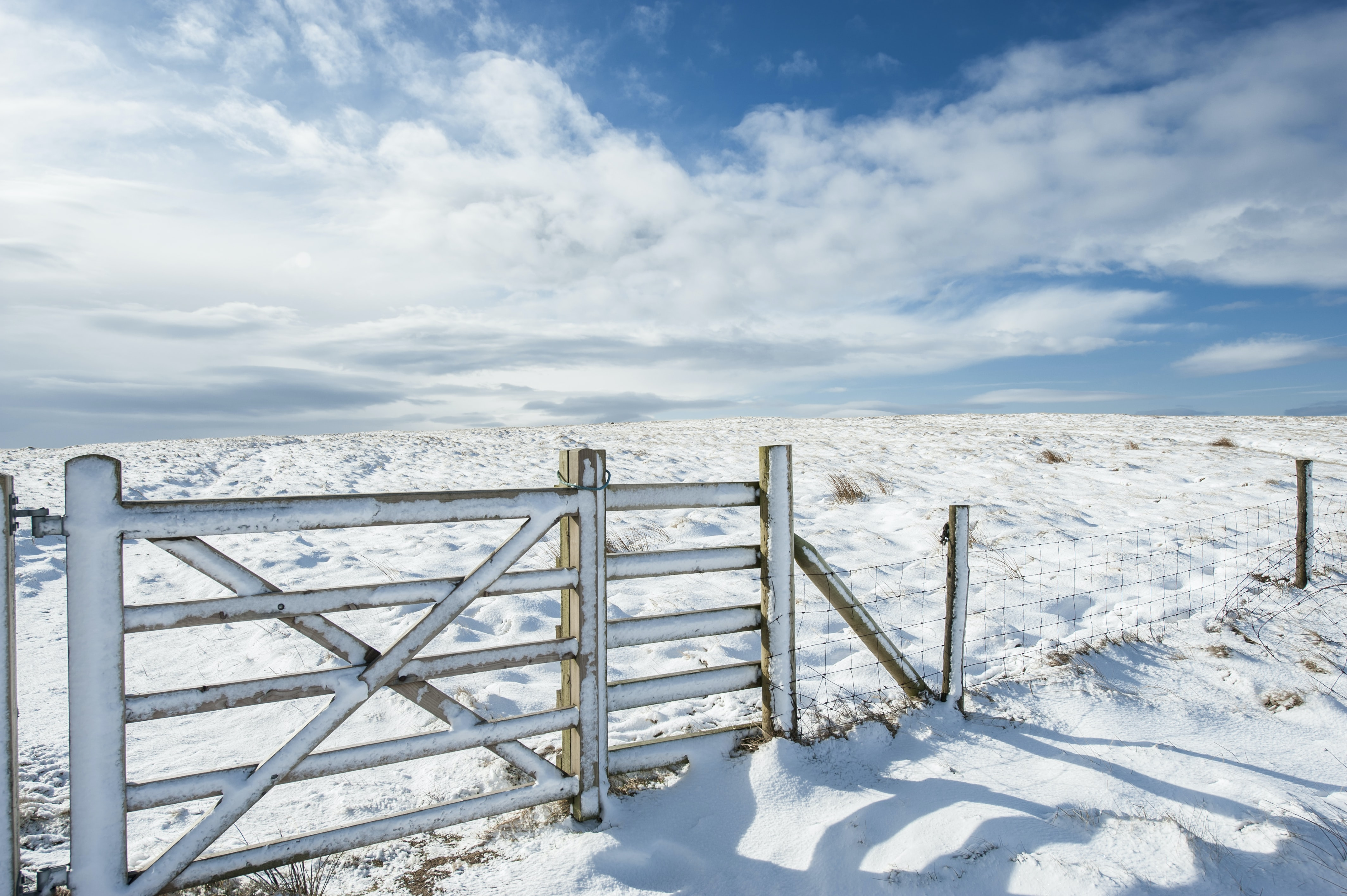 A snow covered fence going across a field in West Yorkshire