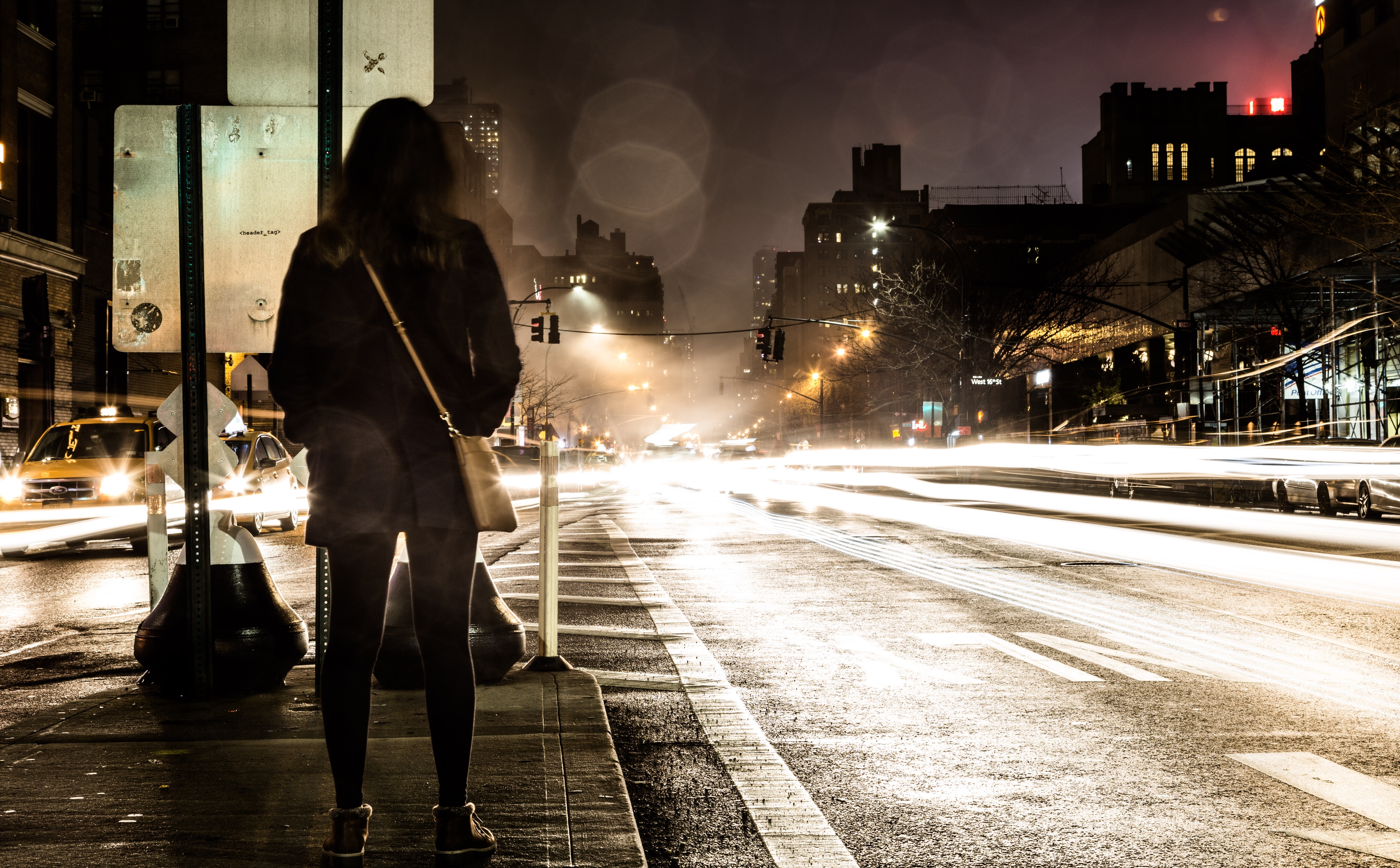 A woman with a leather bag waiting to cross the street in New York at night