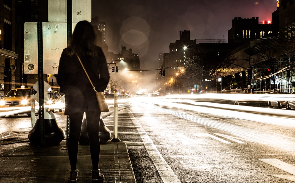 timelapse photography of woman standing near road