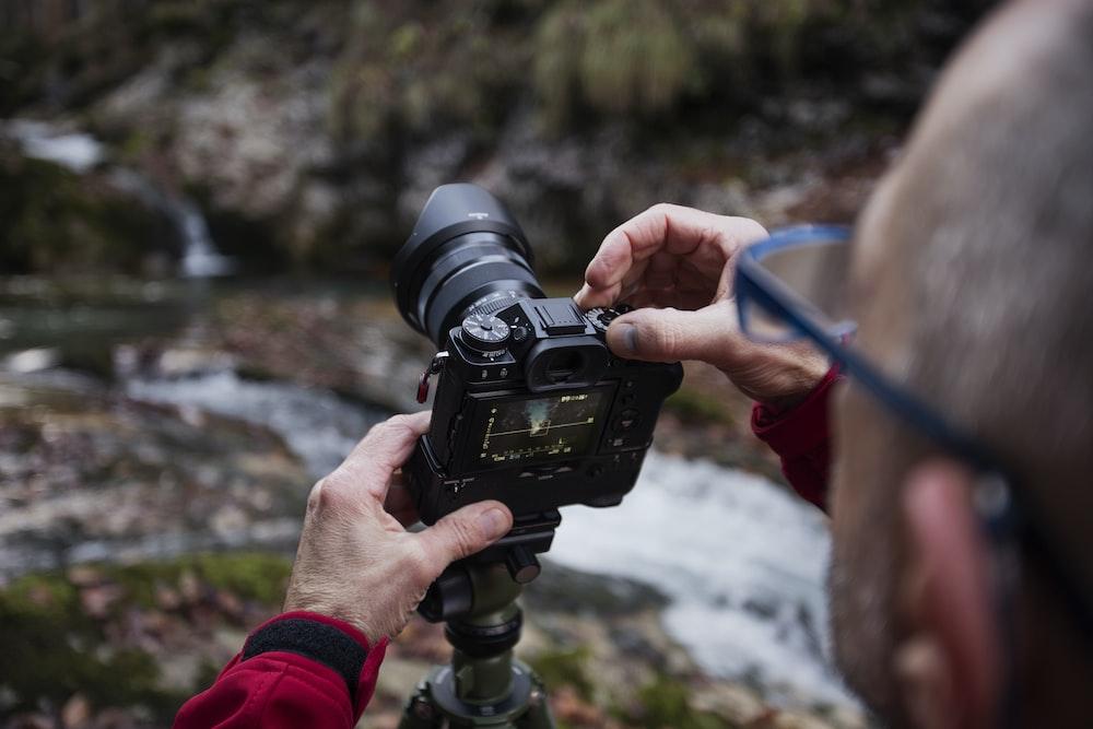 man taking photo of river using DSLR camera