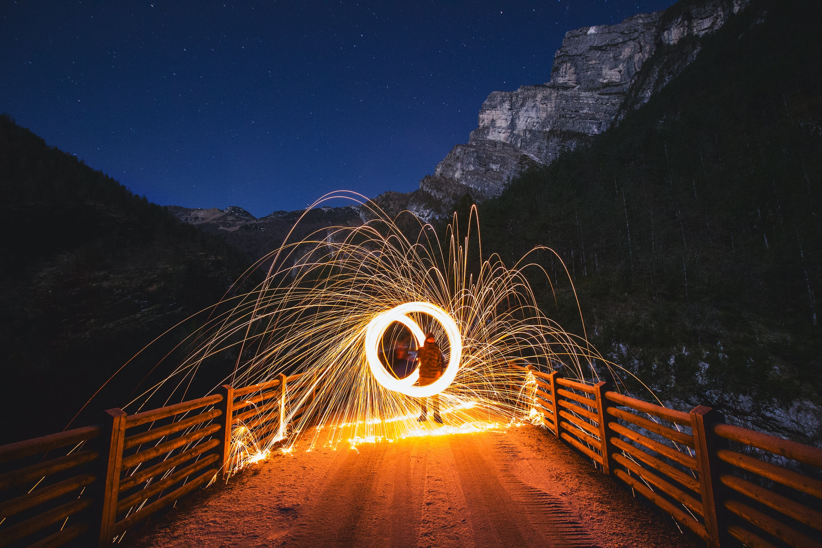 A person spinning sparklers to create circles of light in the mountains