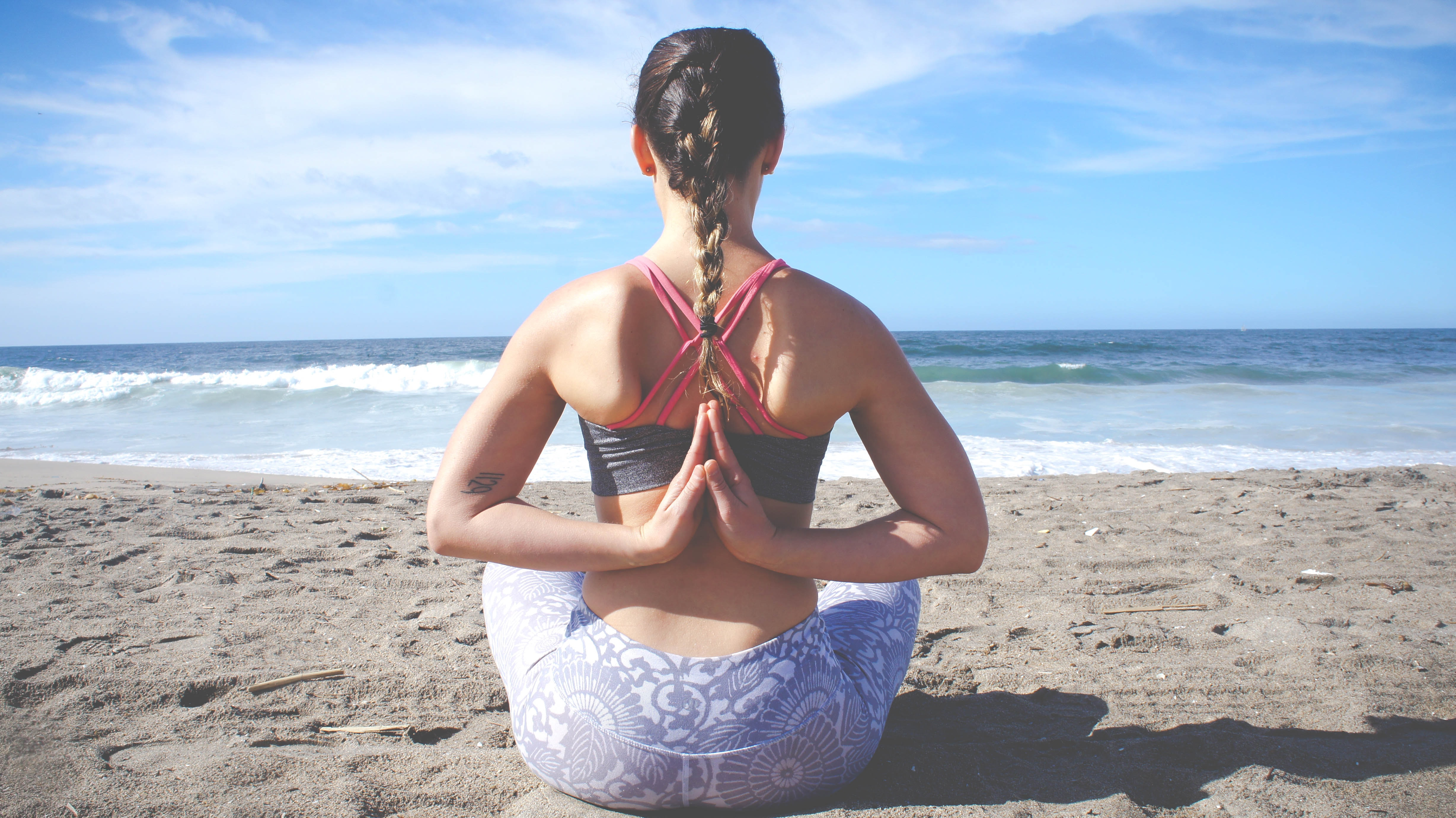 A woman meditating at the beach with her hands behind her back.