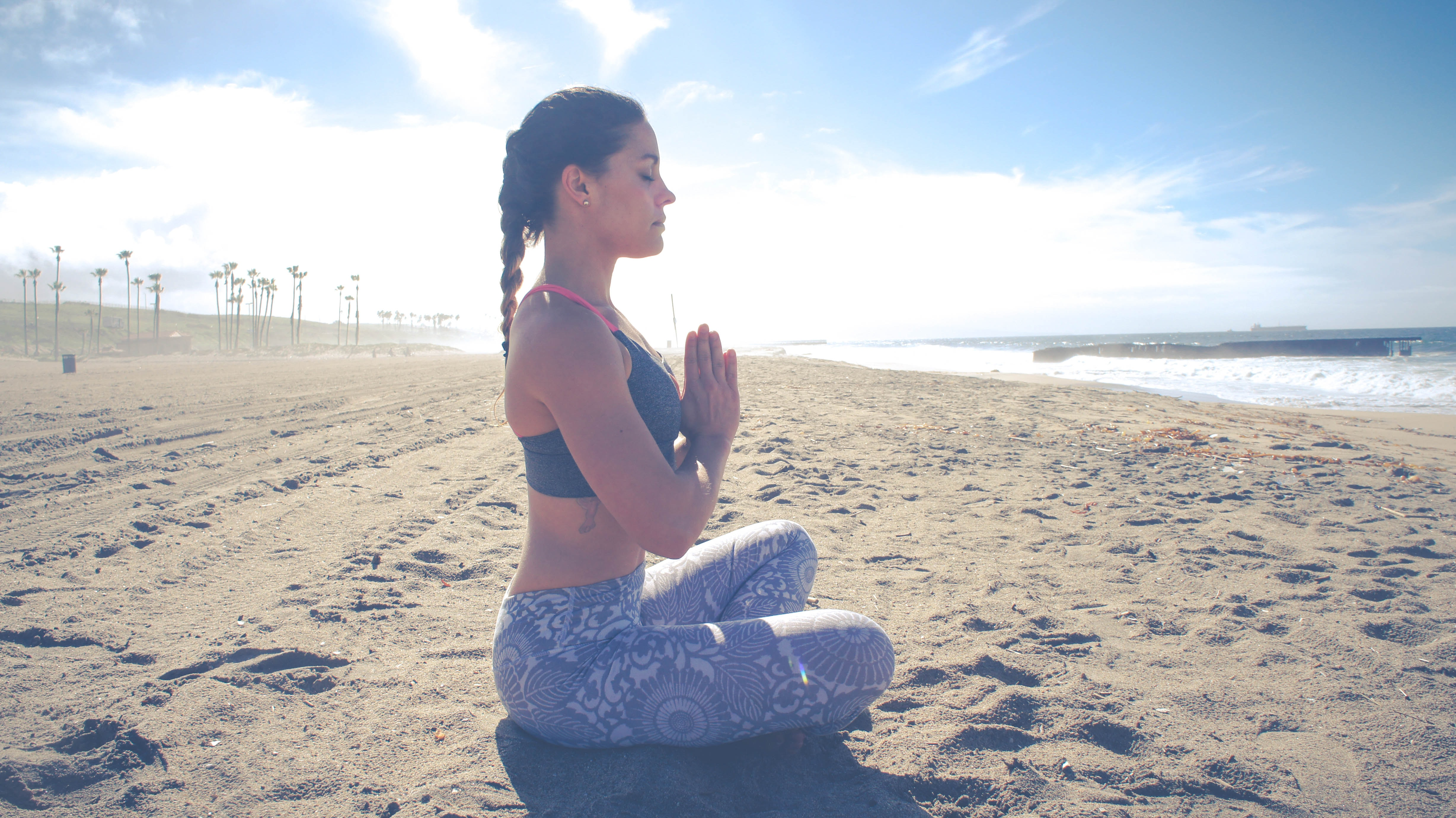 A woman in yoga pants sitting and meditating at the beach.