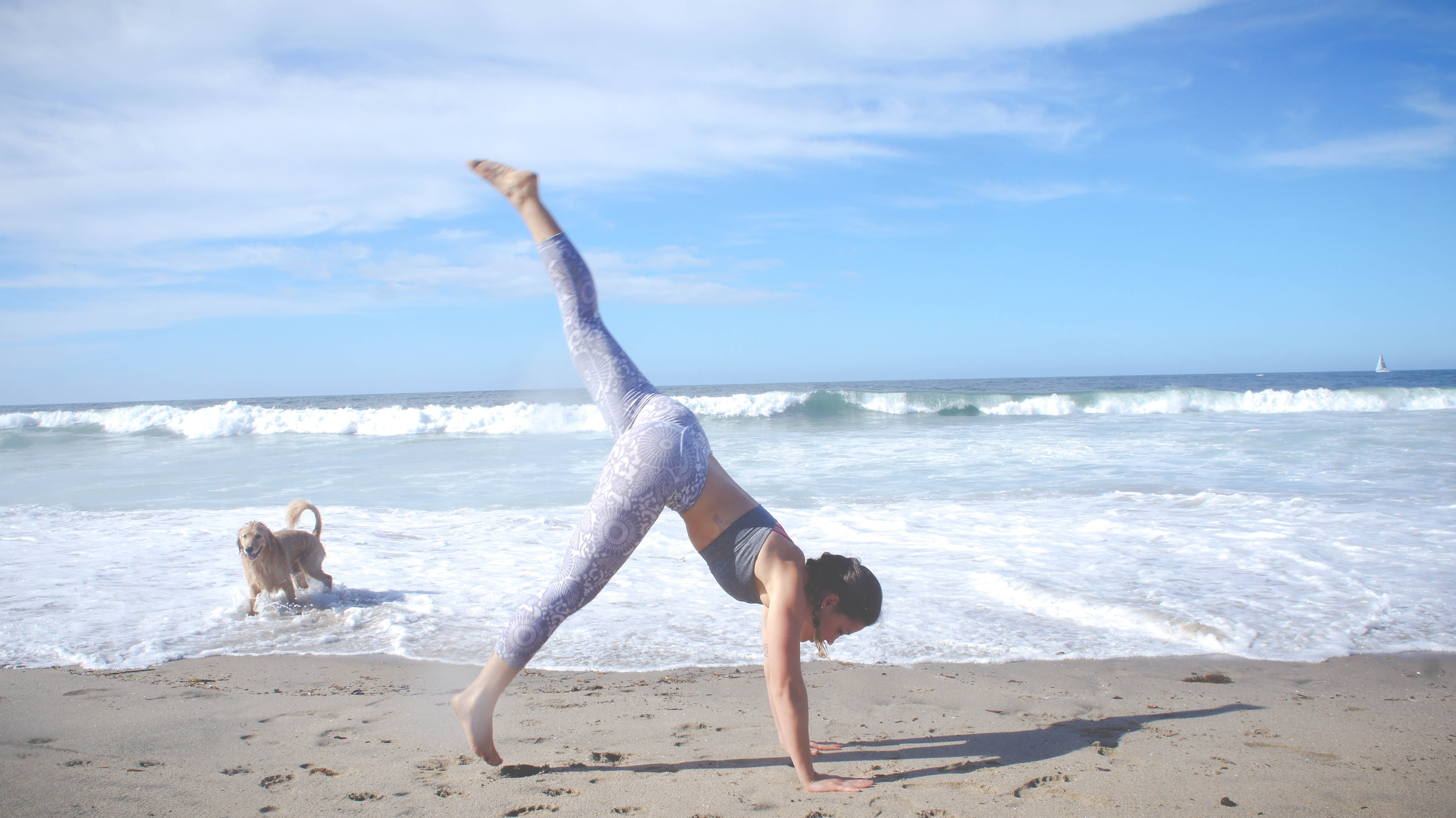 A woman stretching on the beach in yoga pants.