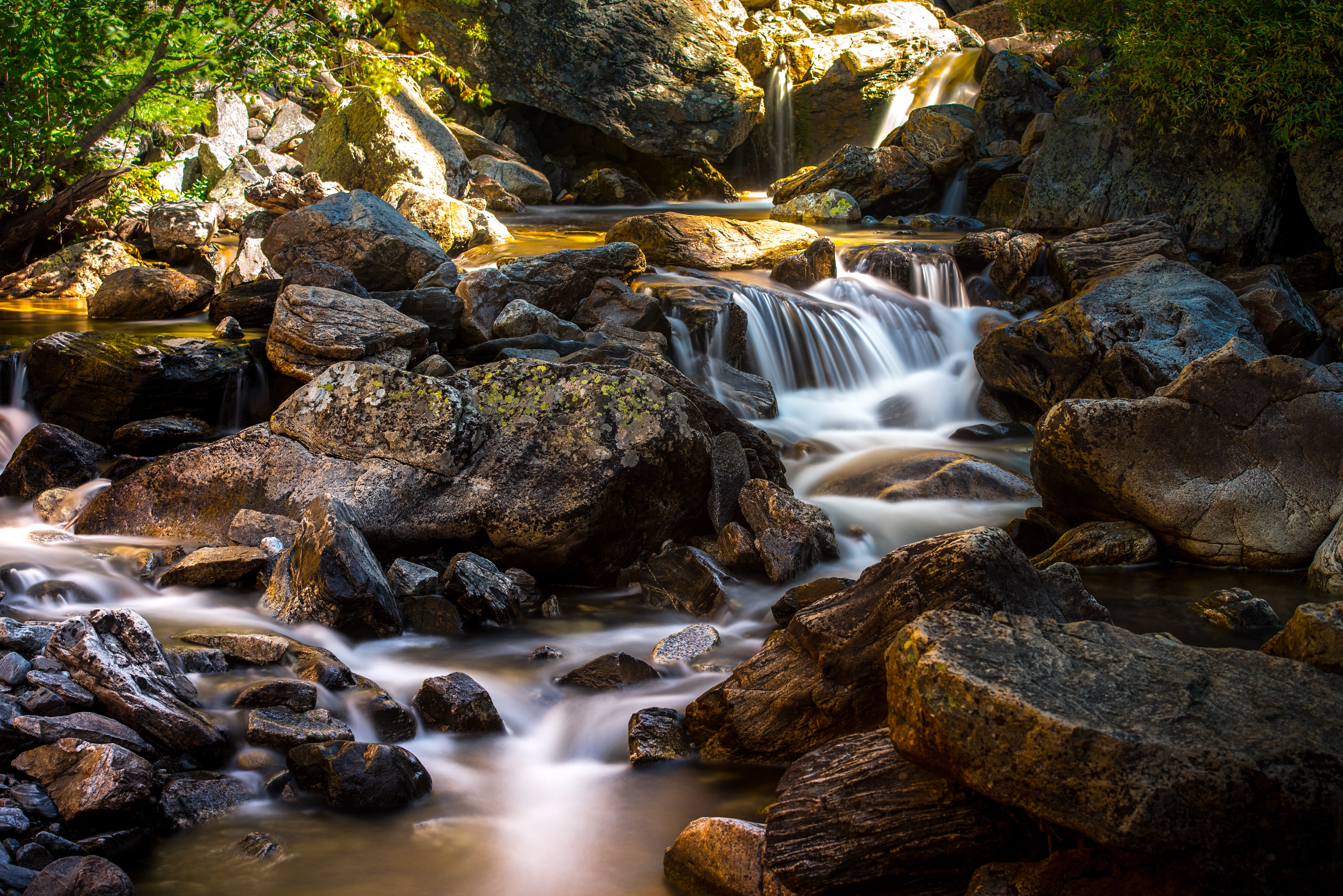A stream flowing through rocks in a creek at the bottom of a stony mountain