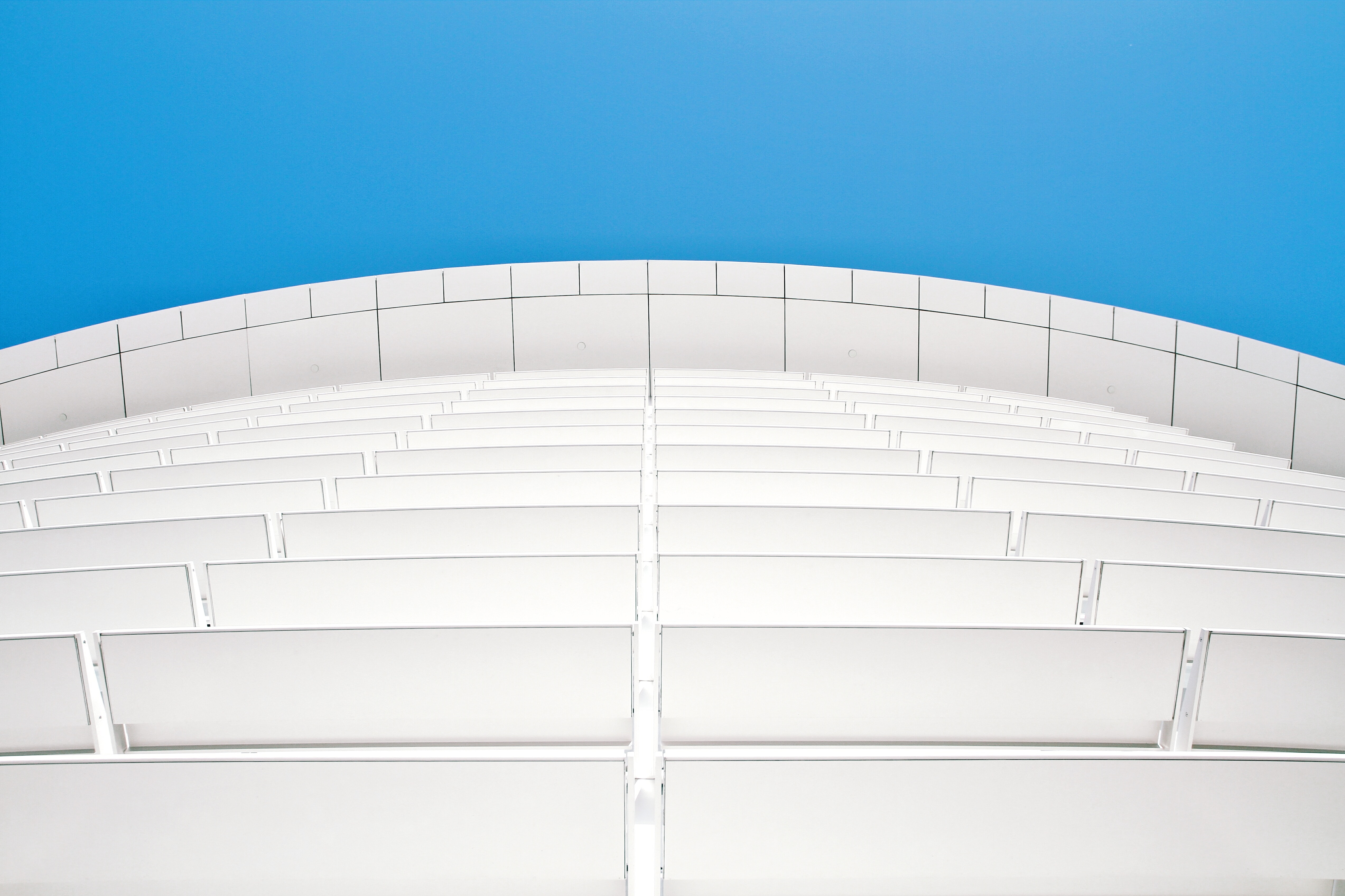 A low-angle shot of a white facade with white panels