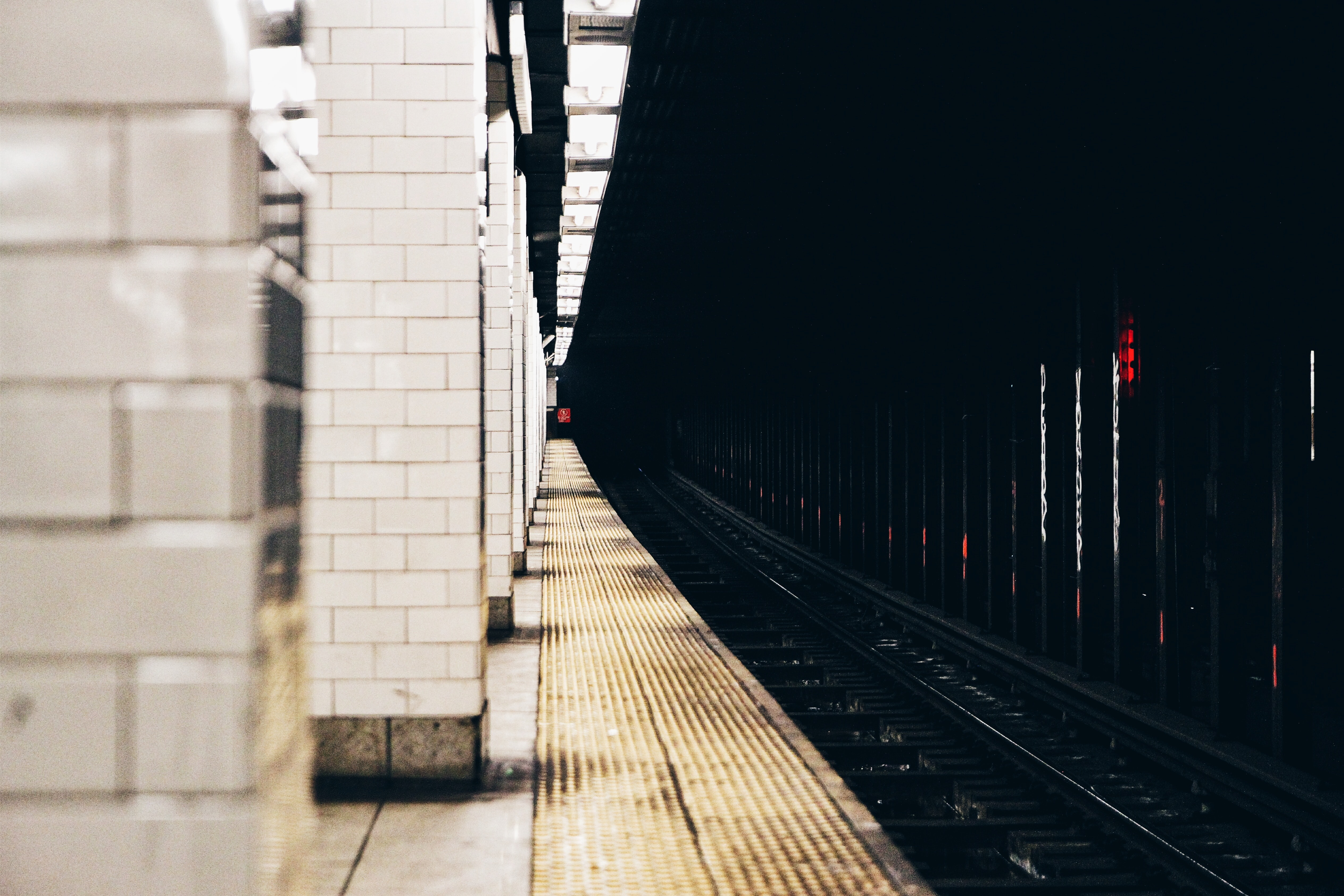 The view from the edge of the platform reveals a long stretch of subway track.