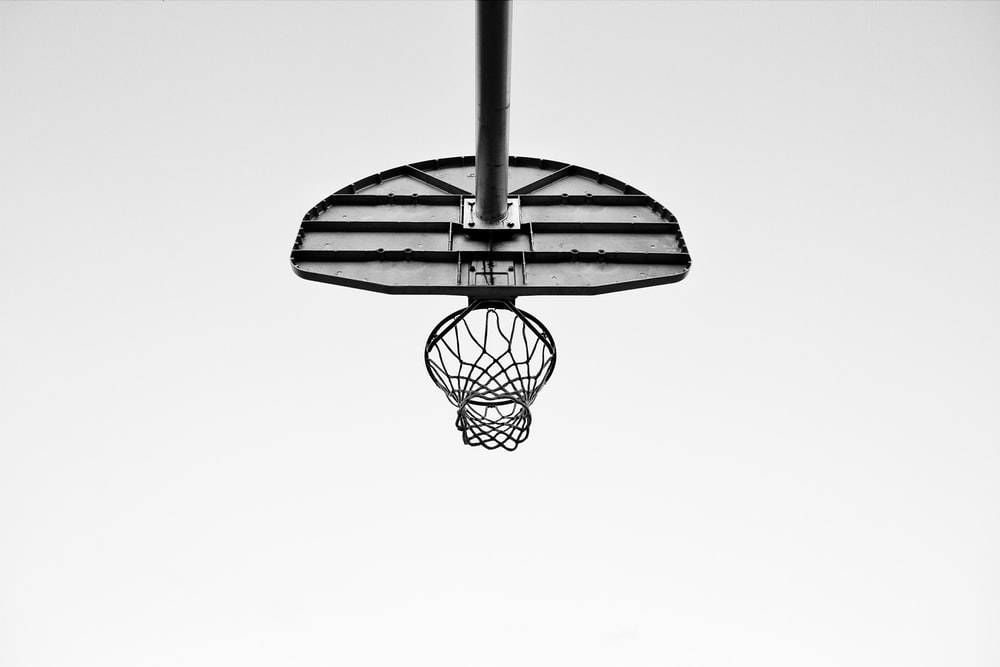 Black And White Image Taken Underneath An Outdoor Basketball Net