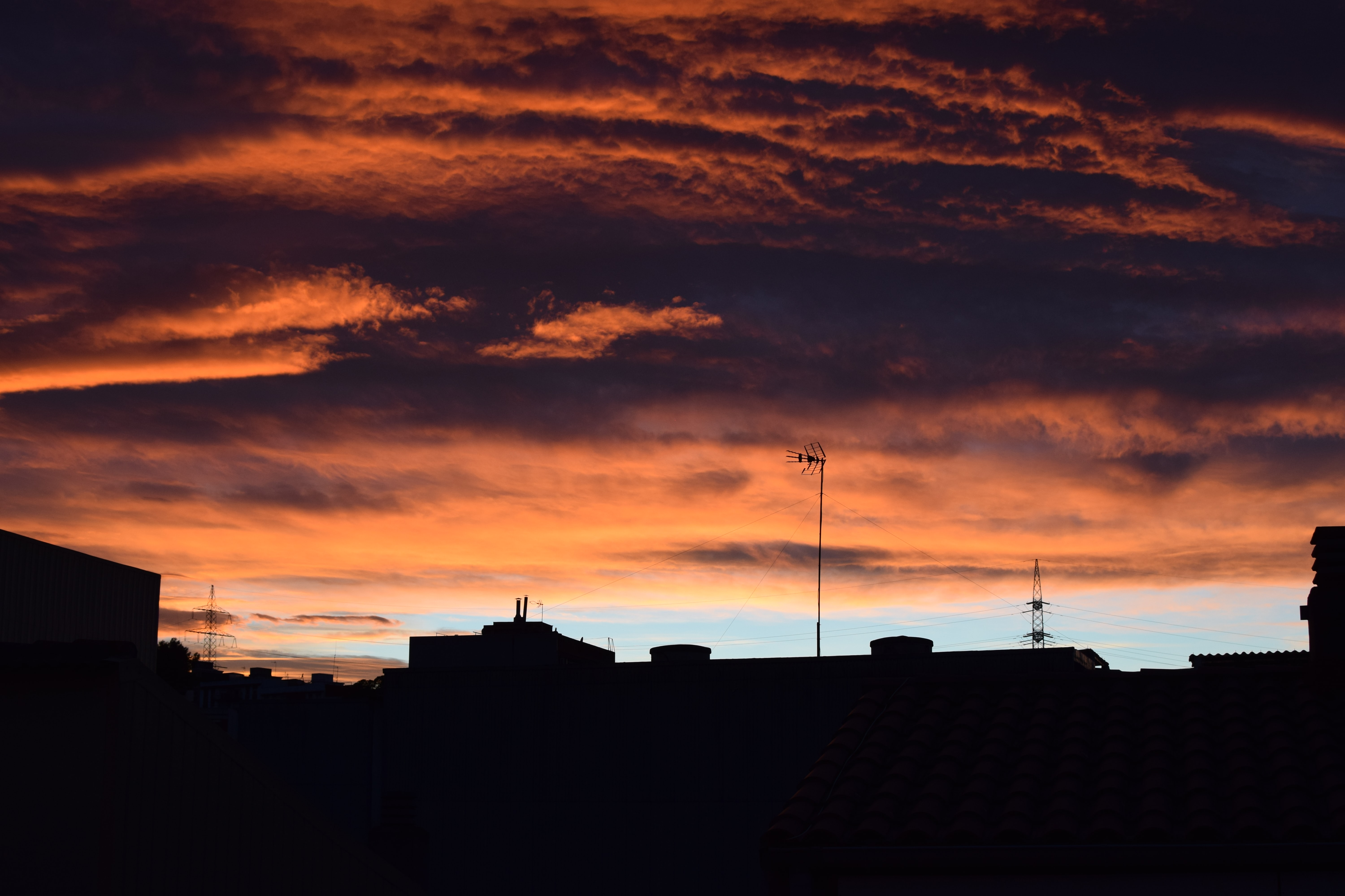 Silhouetted buildings beneath a cloudy sunset in urban Barcelona