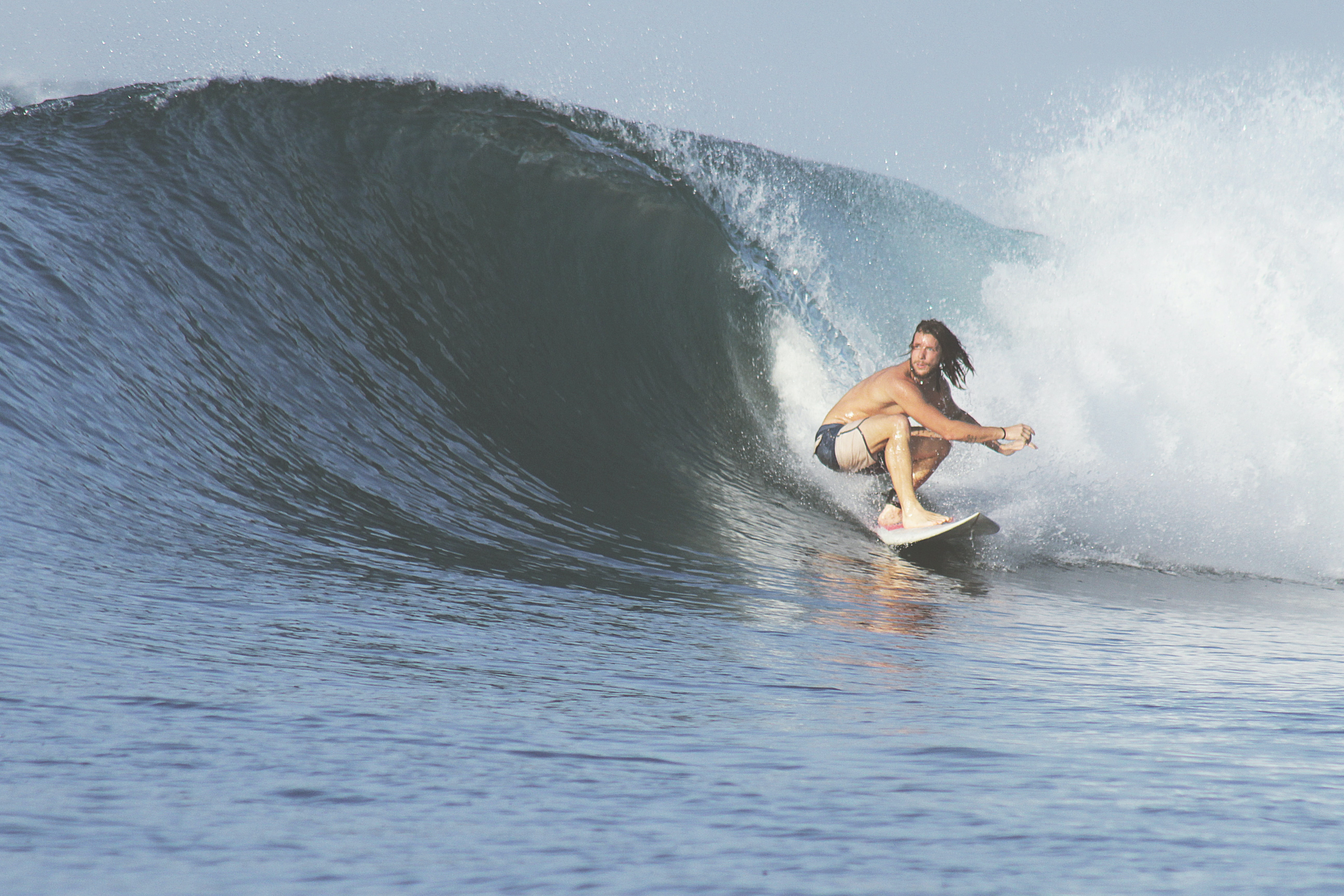 A male surfer with long head, wearing board shorts, crouching as he rides a cresting wave at Sumbawa