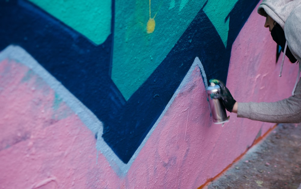 person in hoodie making a graffiti art