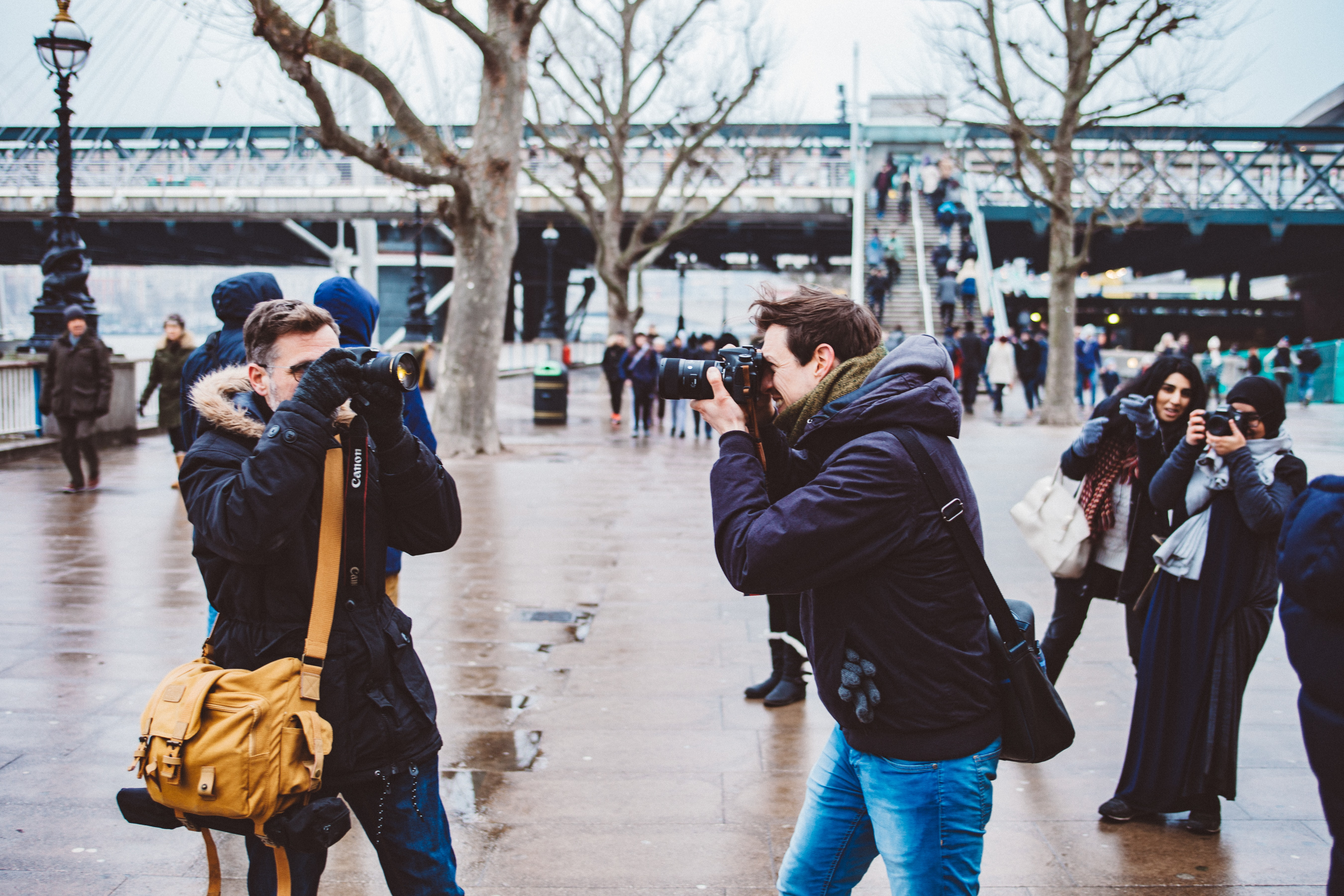 Three photographers taking pictures of each other on a street in South Bank