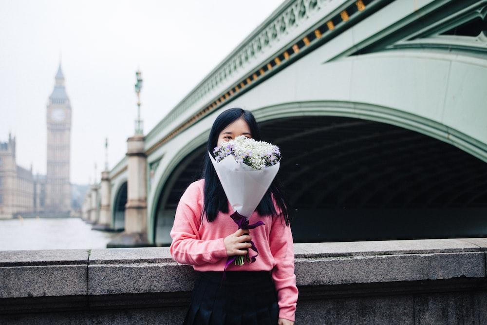 woman holding flower bouquet standing beside concrete railings