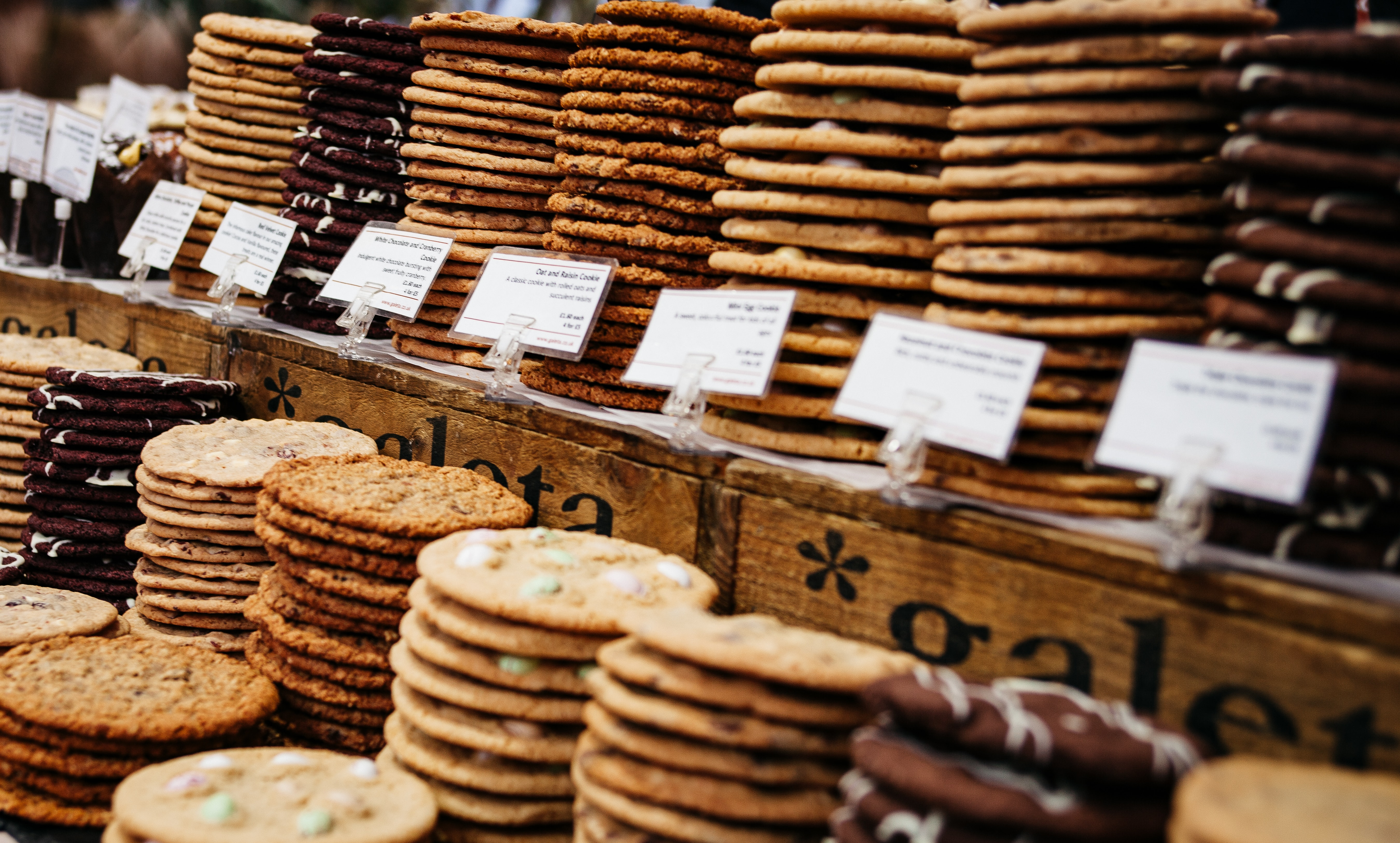A display of several different kinds of cookies at a bakery