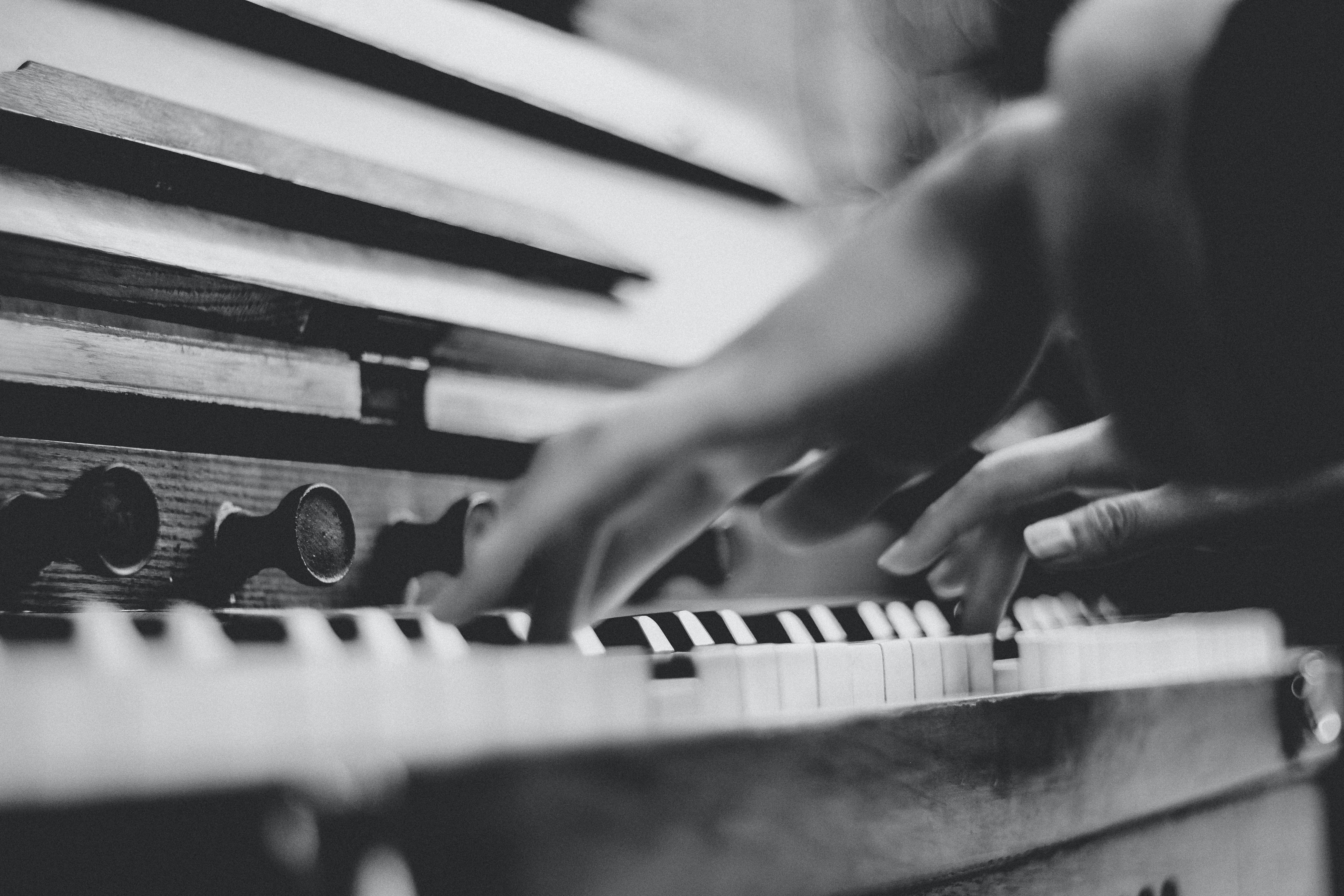 A low-angle black-and-white shot of a person playing the piano