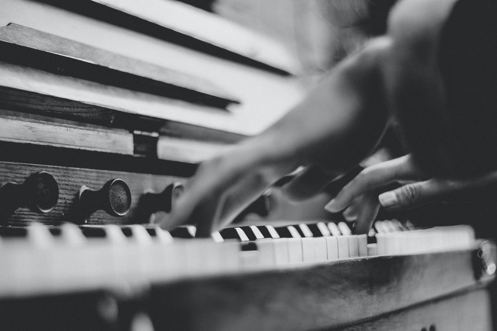 gray scale photo of person playing piano