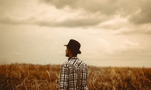 man wearing black hat standing on brown field during daytime