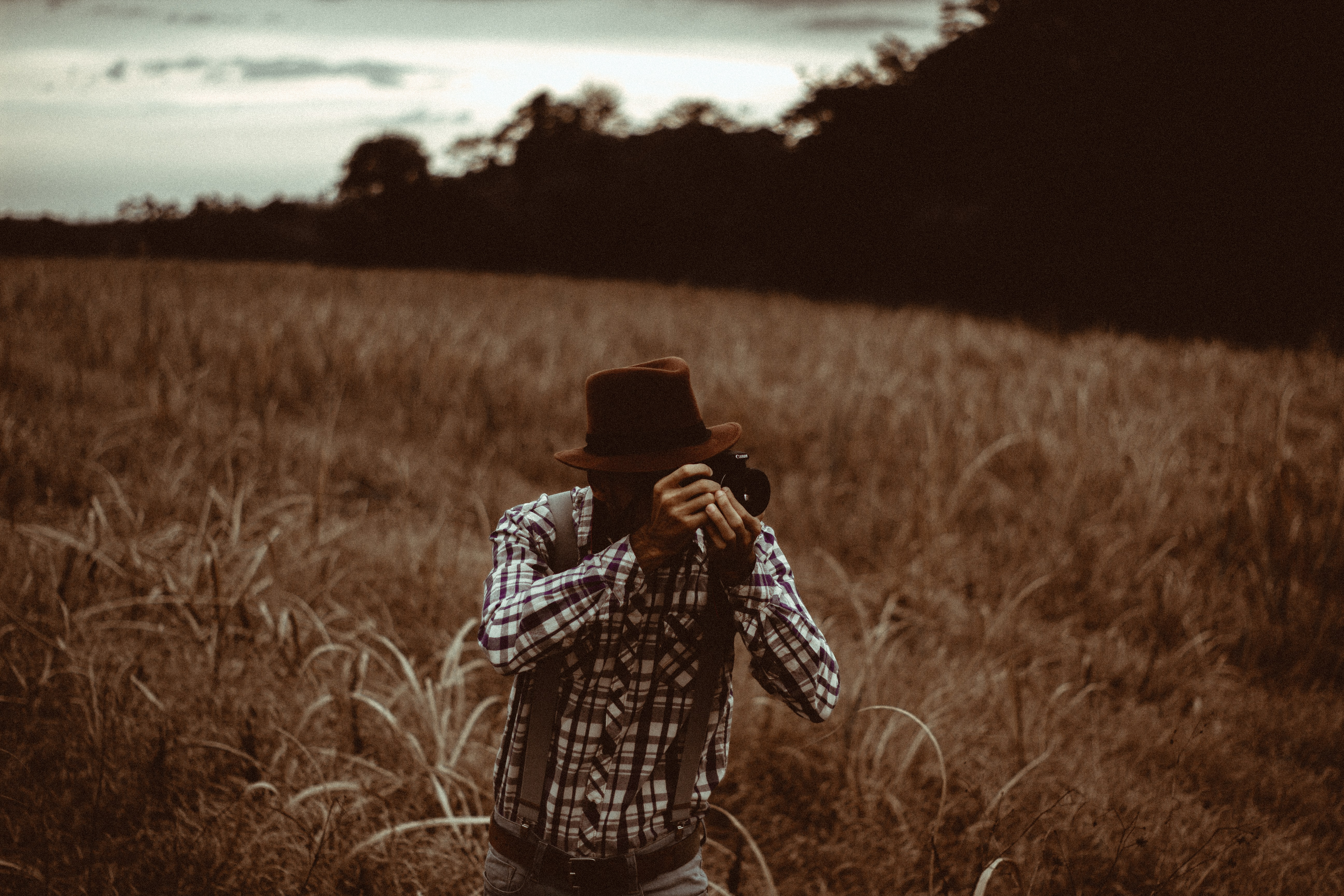 A man in a brown hat and suspenders kneels, taking a photo, in a field