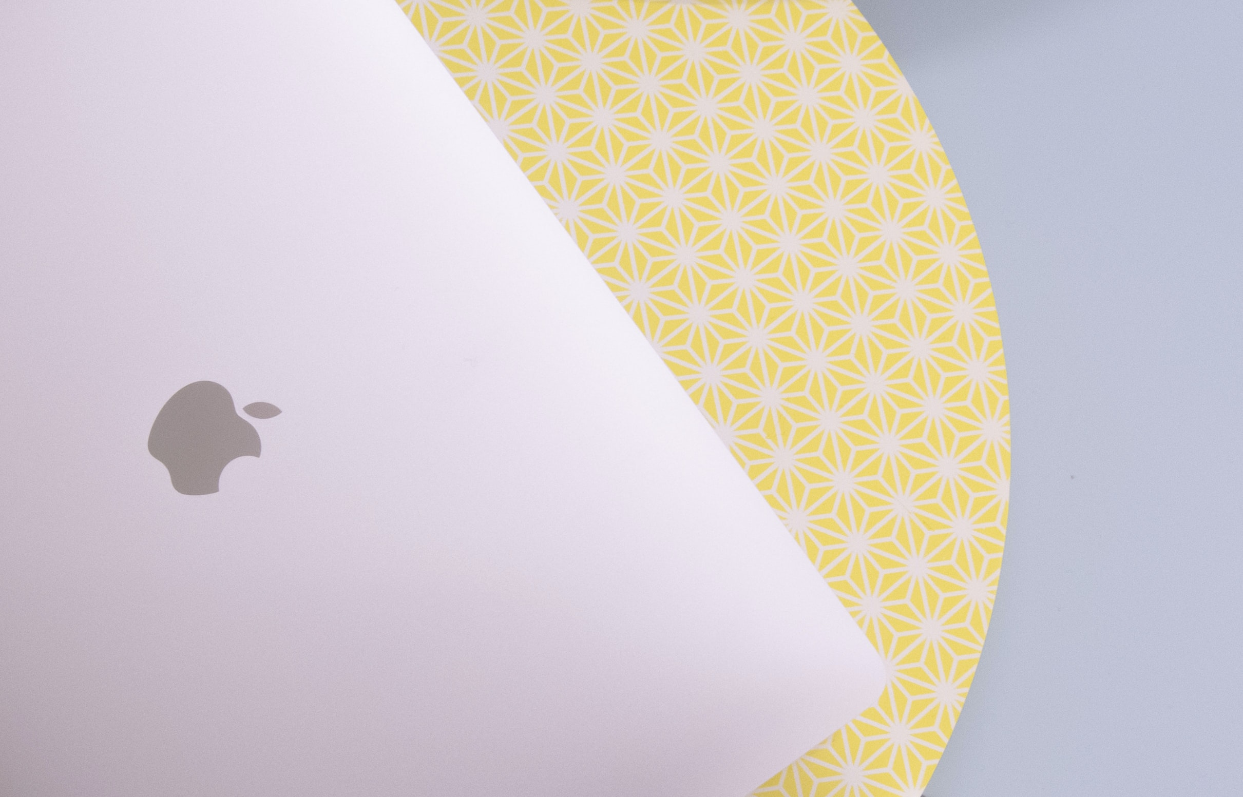 A MacBook laptop on a yellow patterned table in London