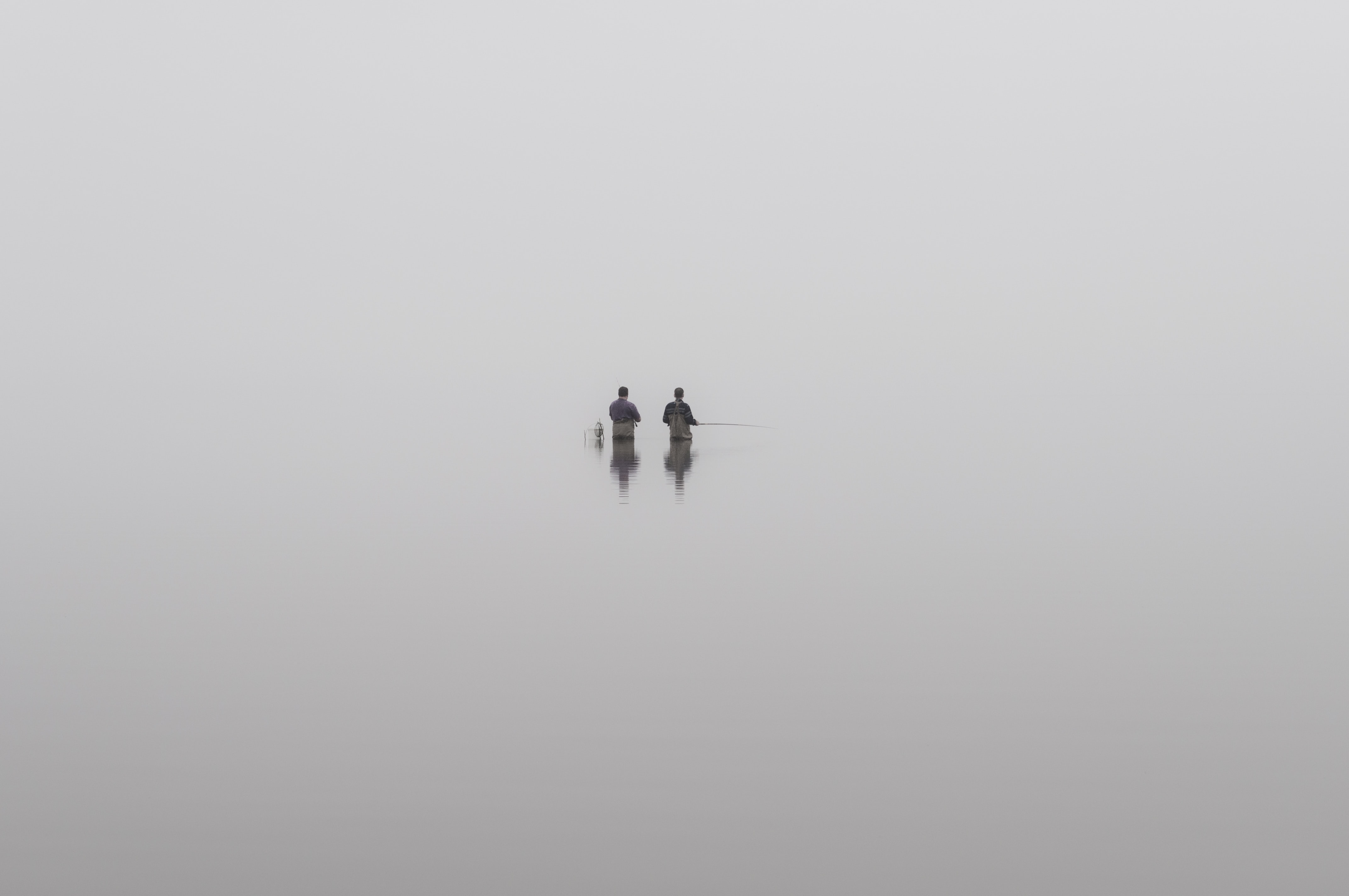 two people holding fishing rod in boat