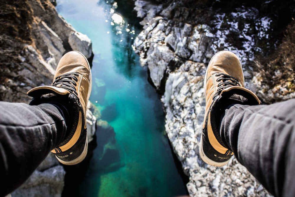 persons feet on body of water
