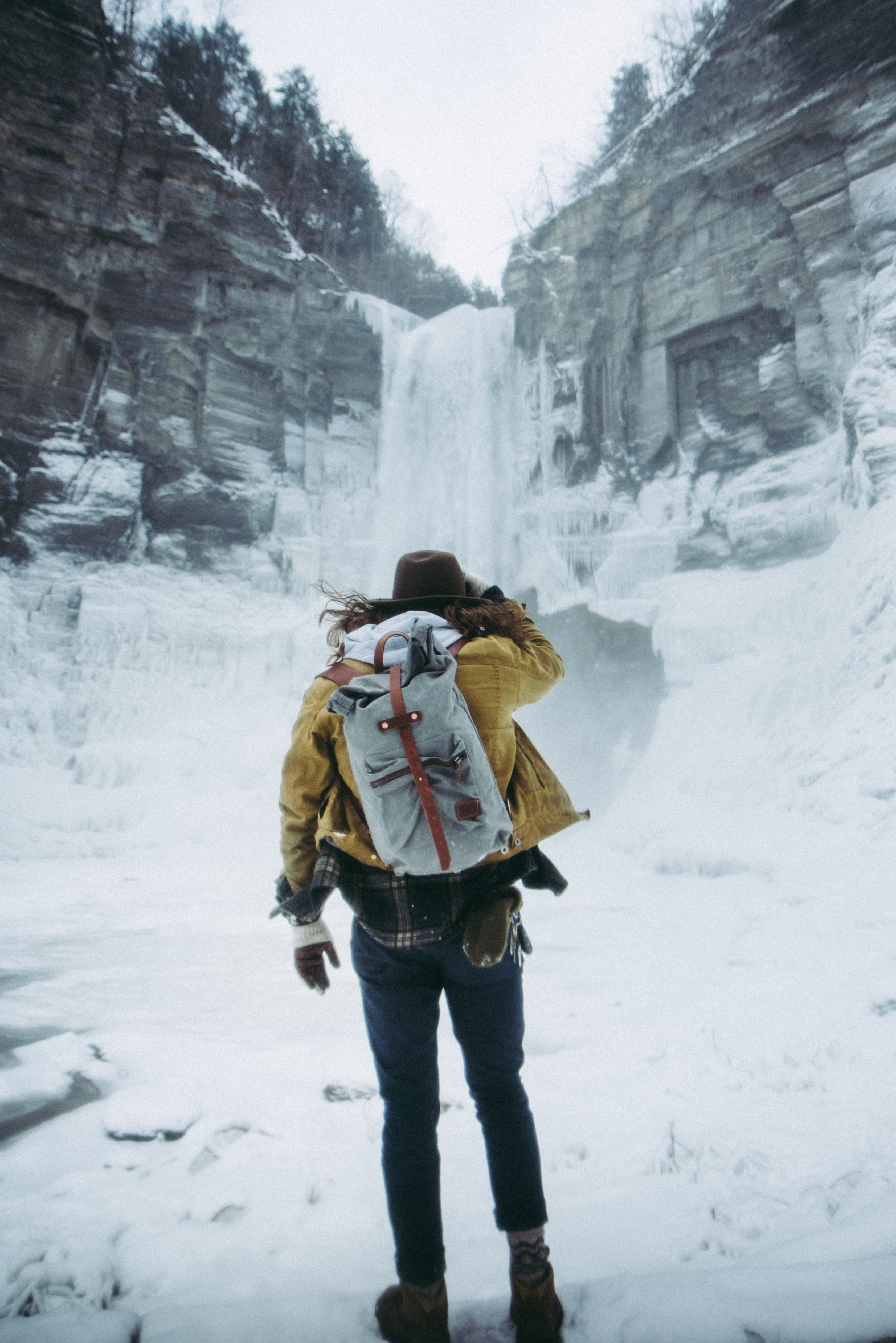 A hiker staring at a winter waterfall from the bottom of a mountain in Ithaca, New York