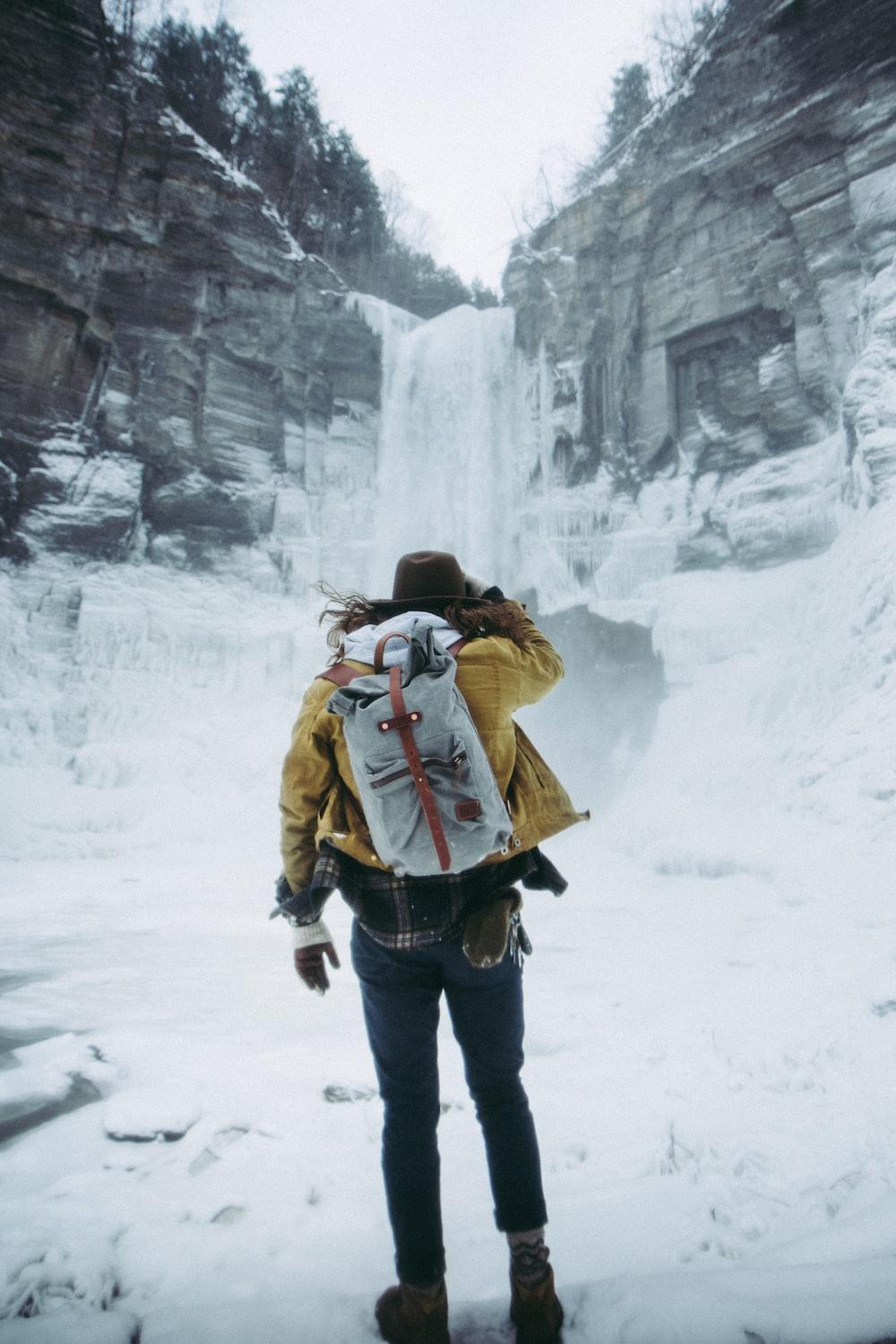 woman facing frozen waterfalls