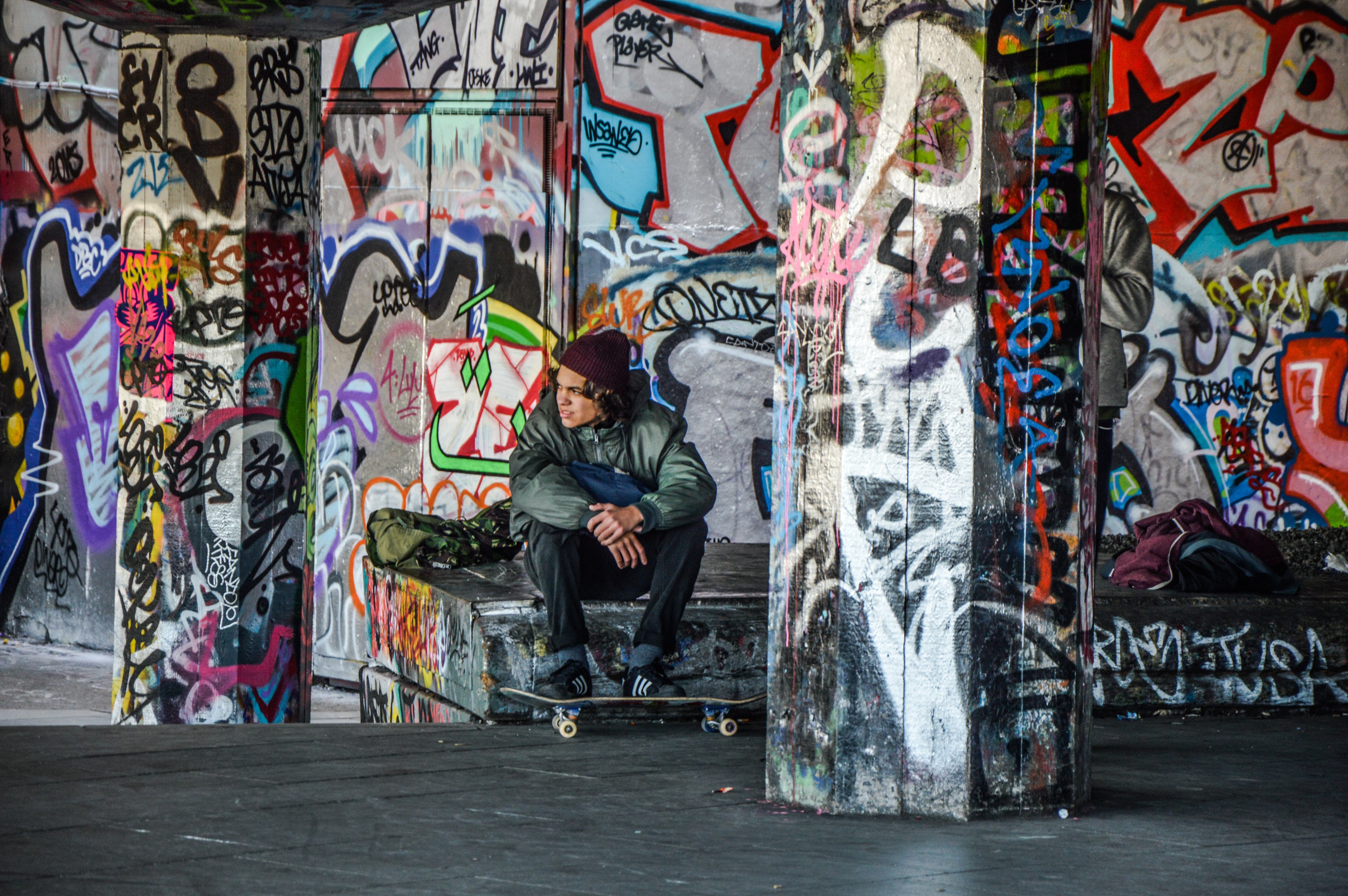 Young man with skateboard sitting in urban area with walls covered in colorful graffiti, London