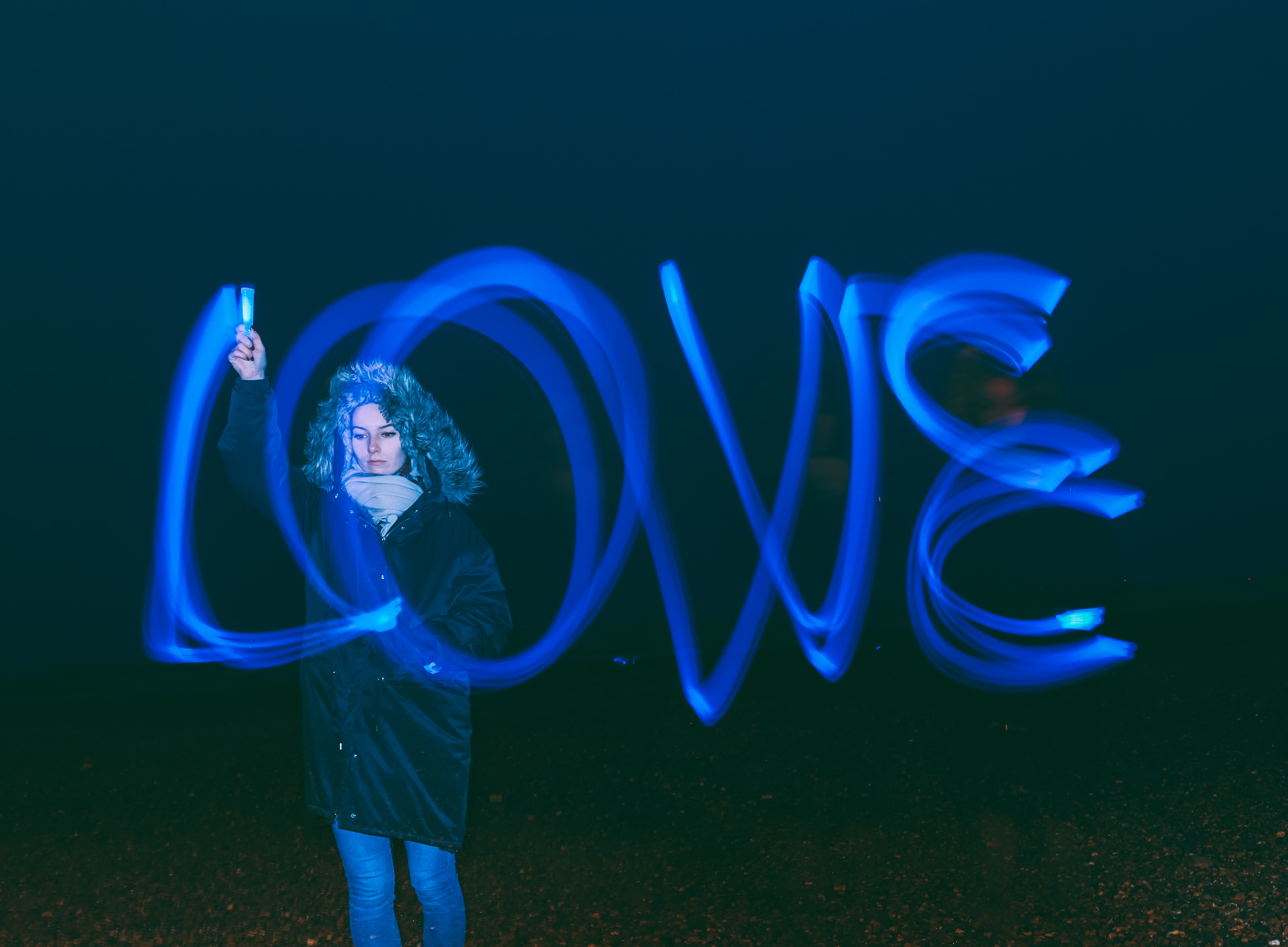 "A woman in a coat uses blue light to paint the word ""LOVE"" in darkness"