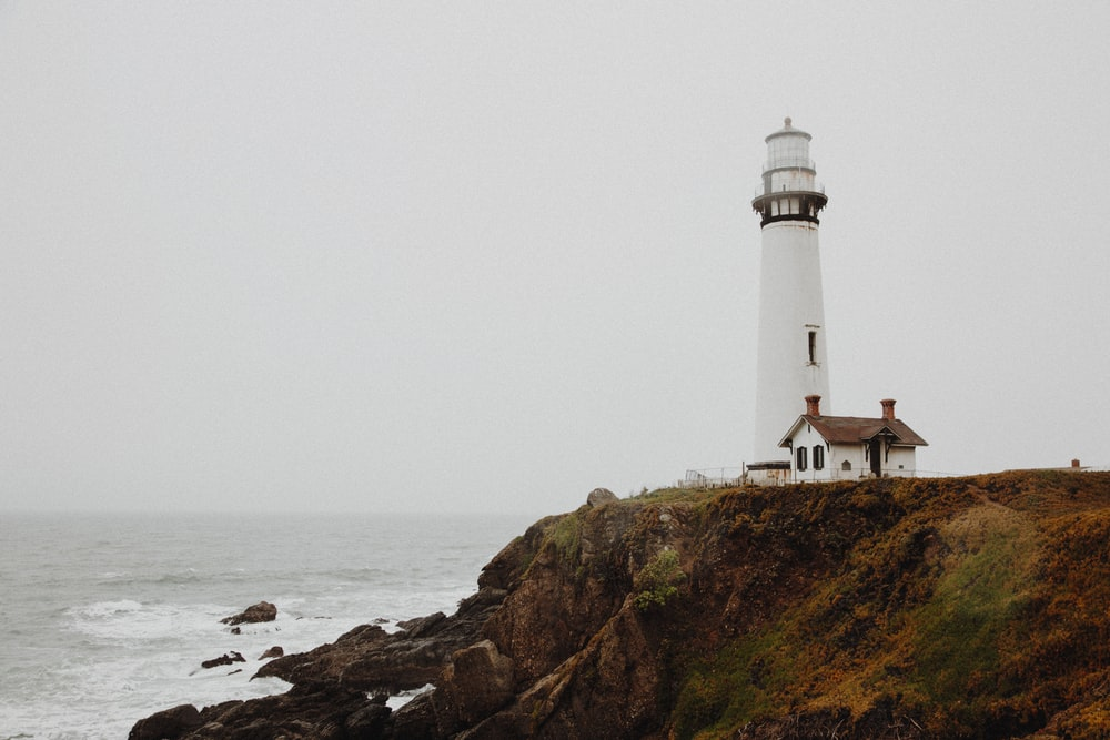 white lighthouse on rocky cliff