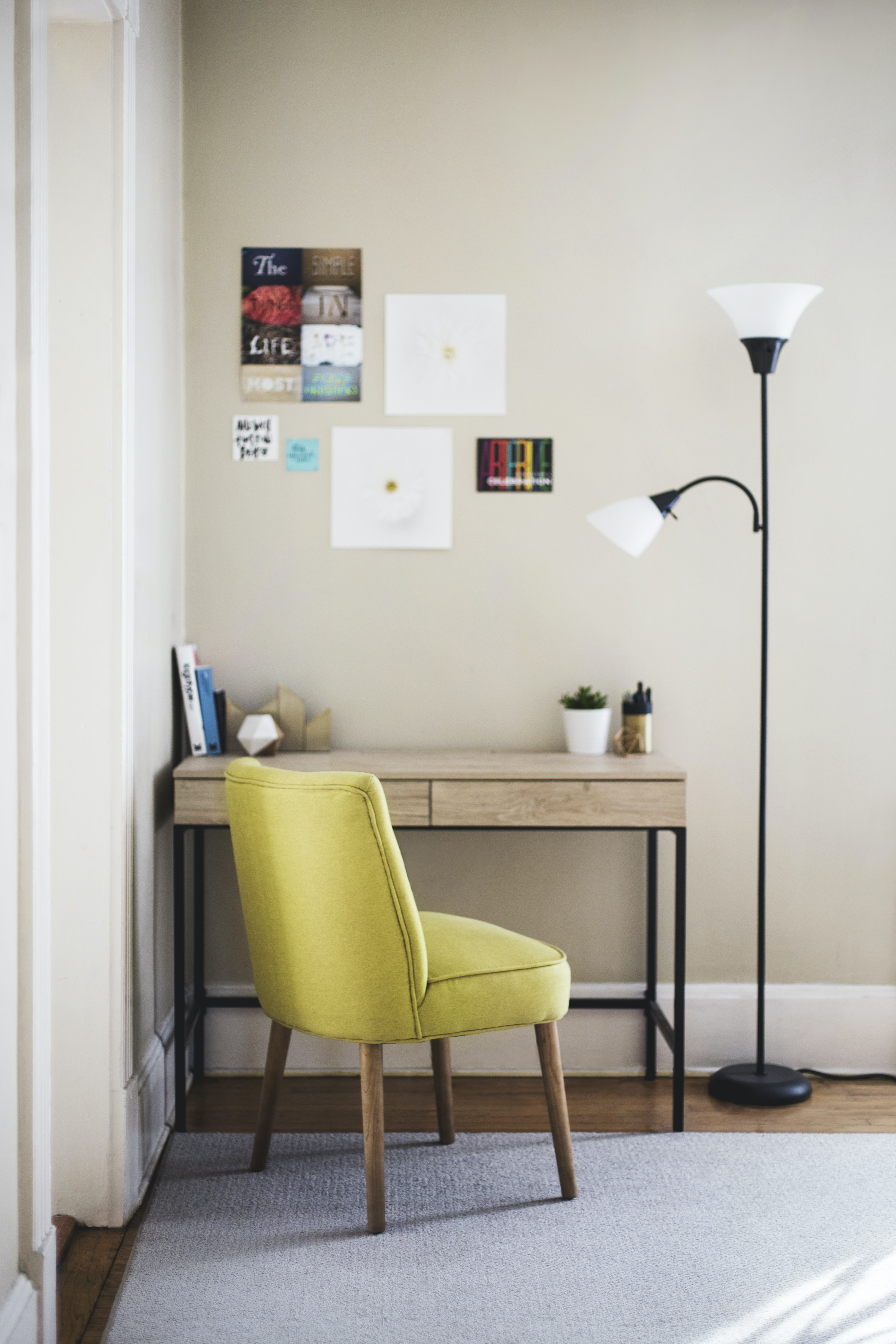 A small desk in the corner of a cozy room with a chair and a floor lamp