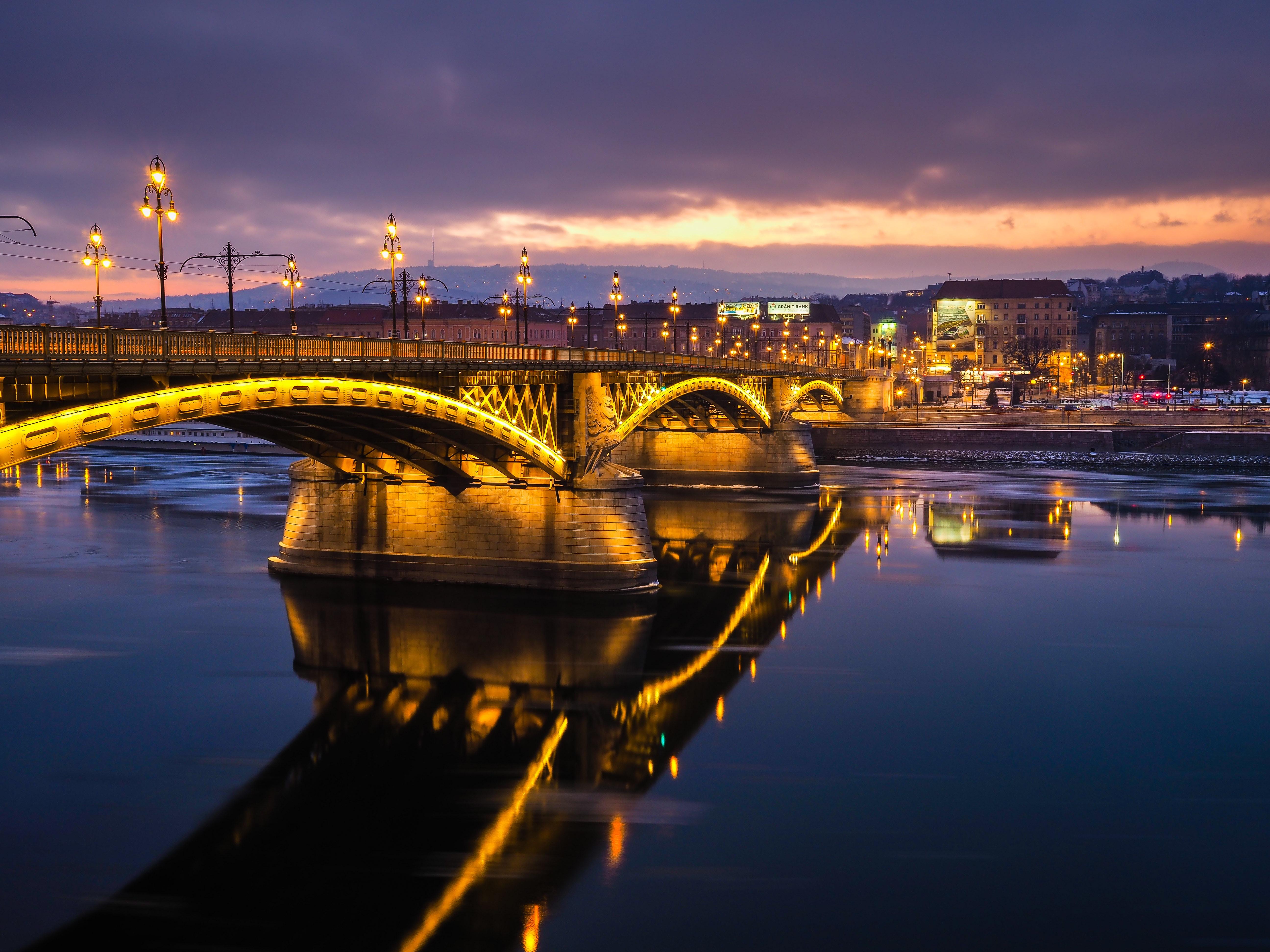 lighted concrete bridge near buildings