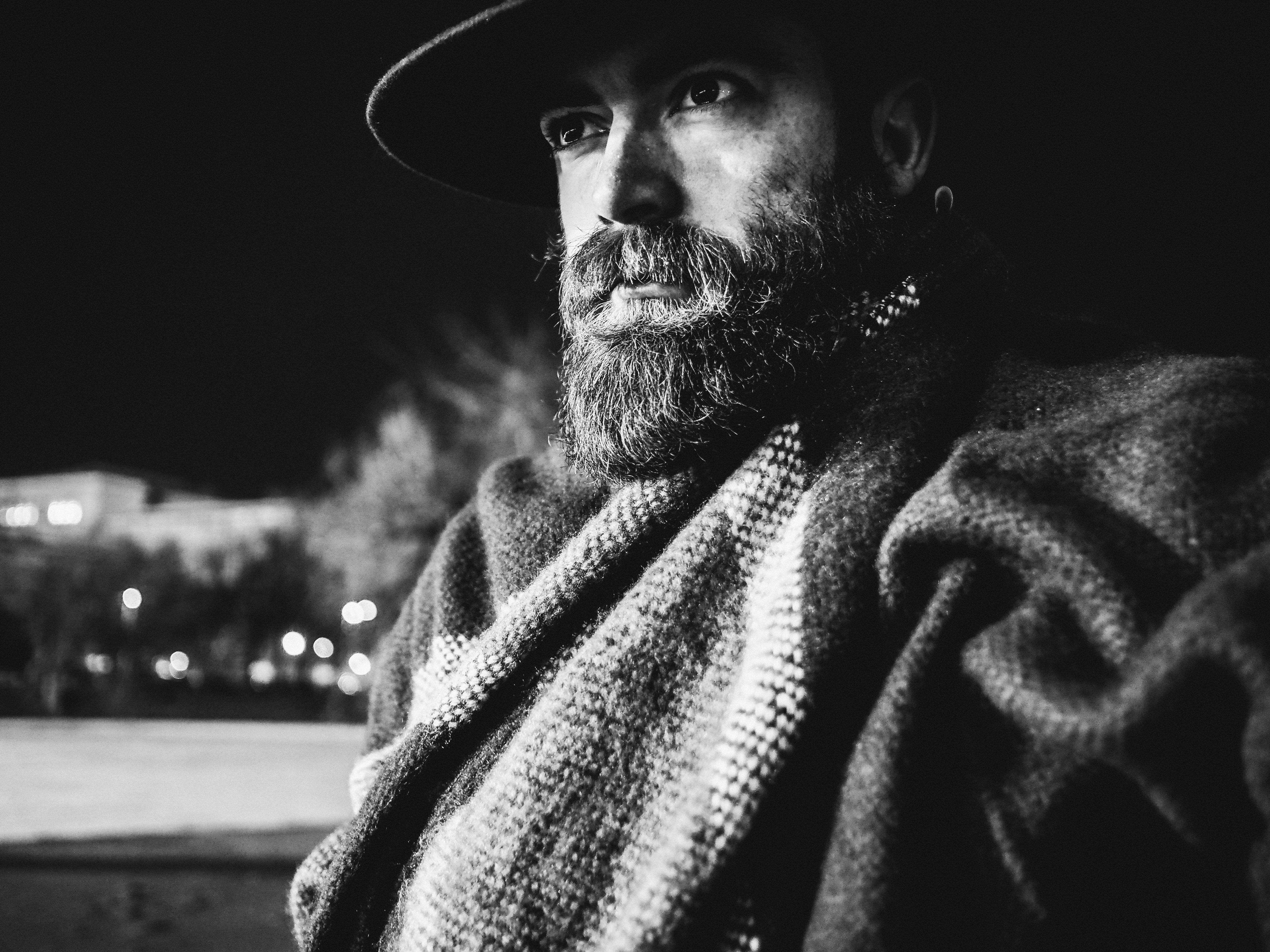 Black and white close up shot of bearded man wearing hat and poncho in budapest