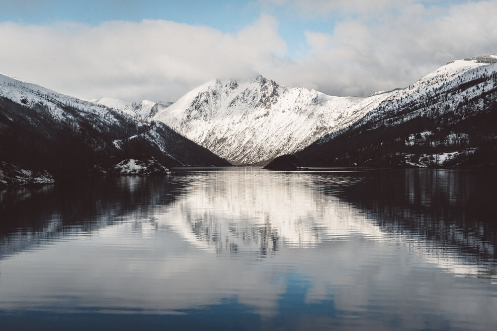reflective photography of snow-covered mountain